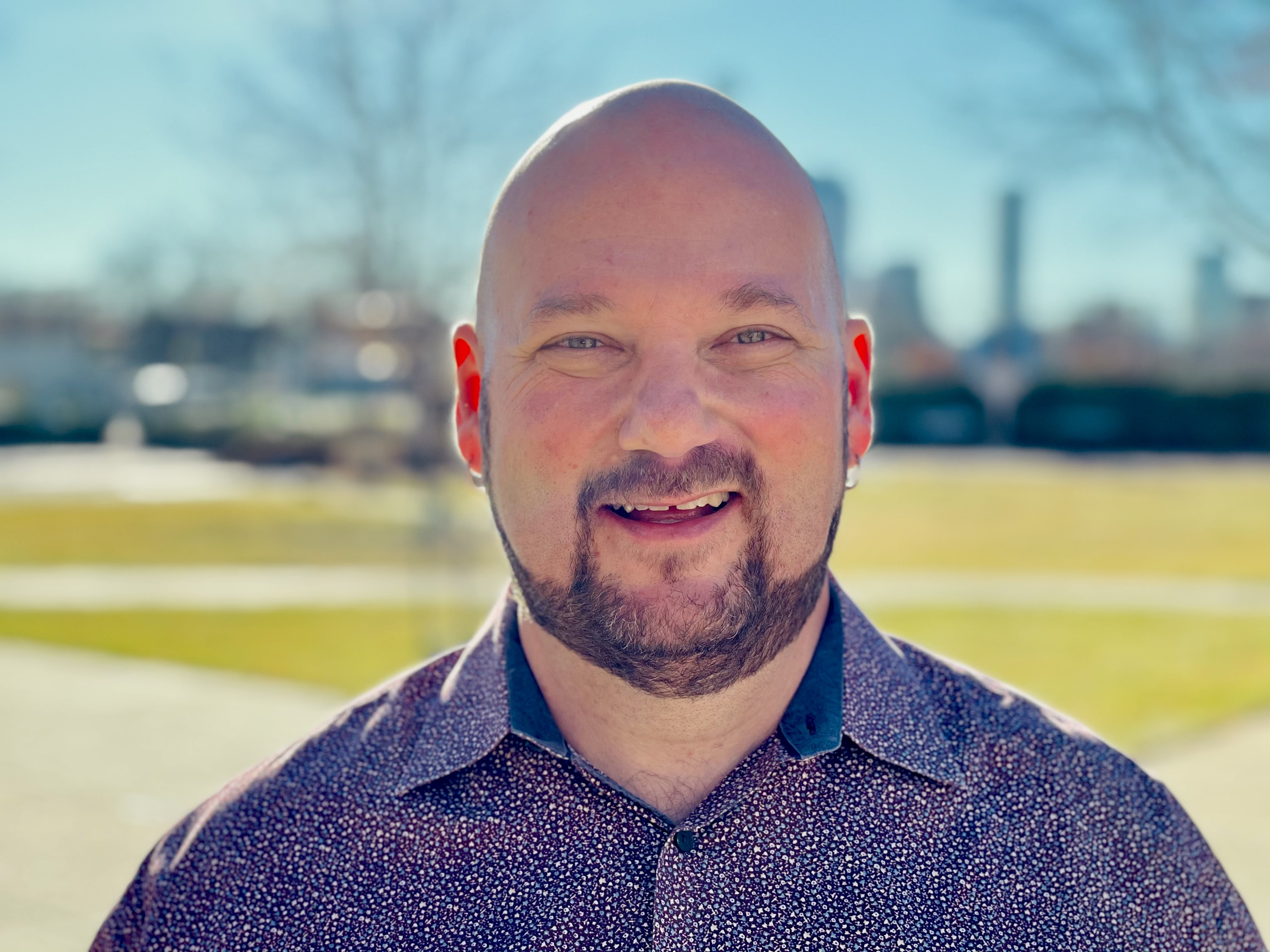 A portrait of Denver School Board candidate Scott Esserman. He is wearing a purple shirt and standing in front of a plaza with triangular spaces of lawn with cars parked behind.