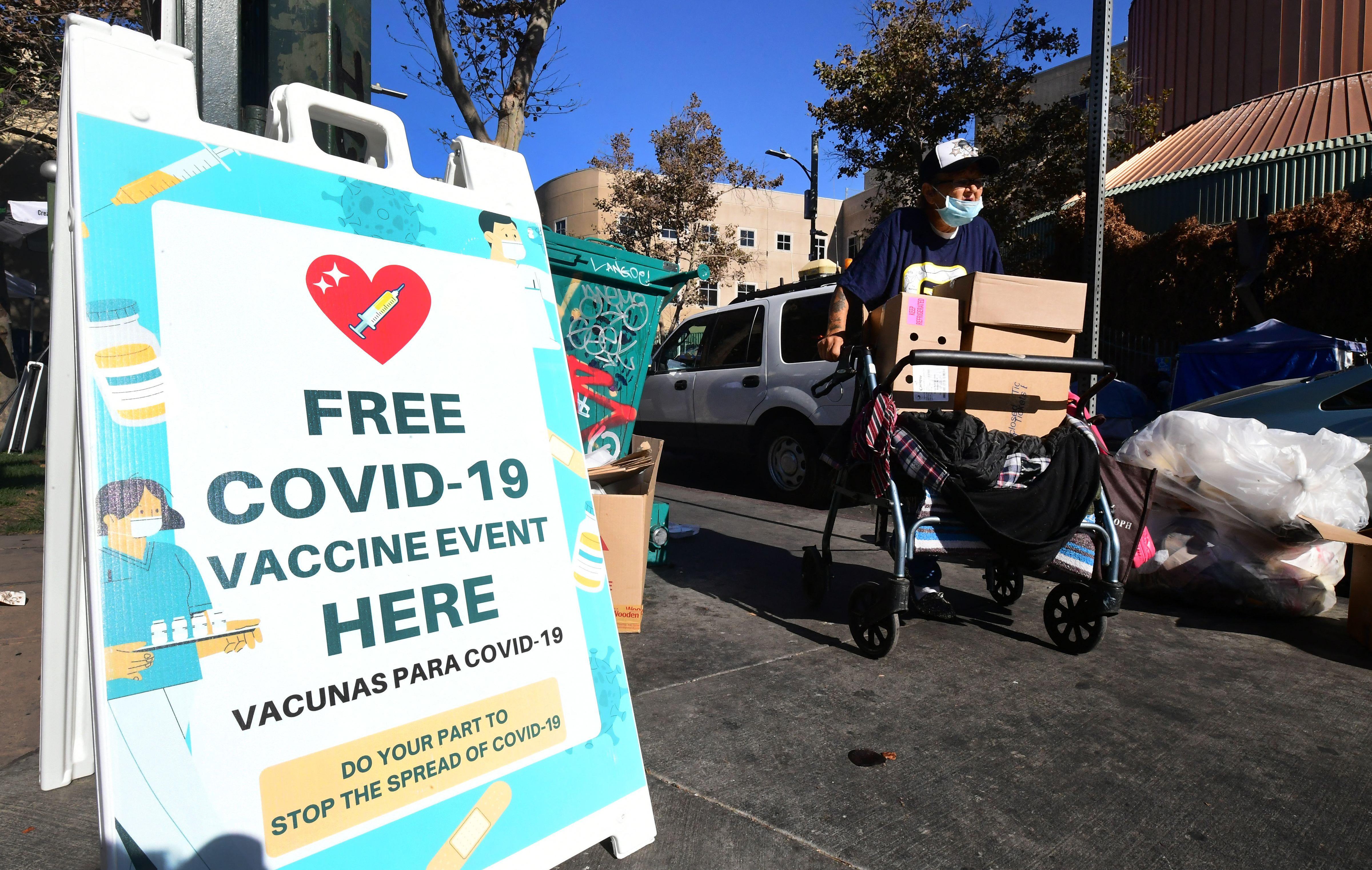 """A sign outside an outdoor vaccination site reads, """"Free Covid-19 vaccine event here."""""""