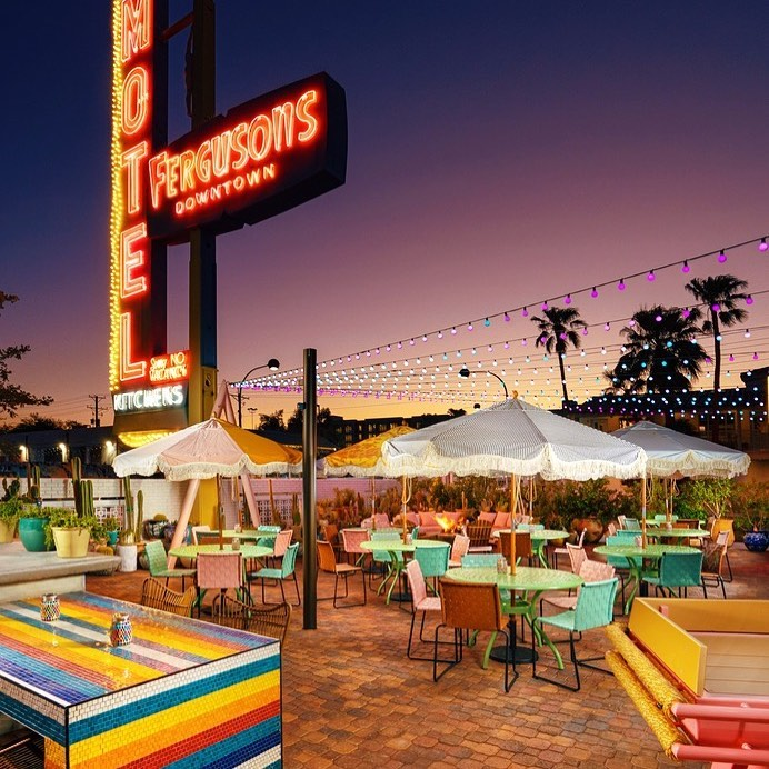 A patio at dusk with a Fergusons Downtown sign in the background, a shuffleboard, and tables with umbrellas.