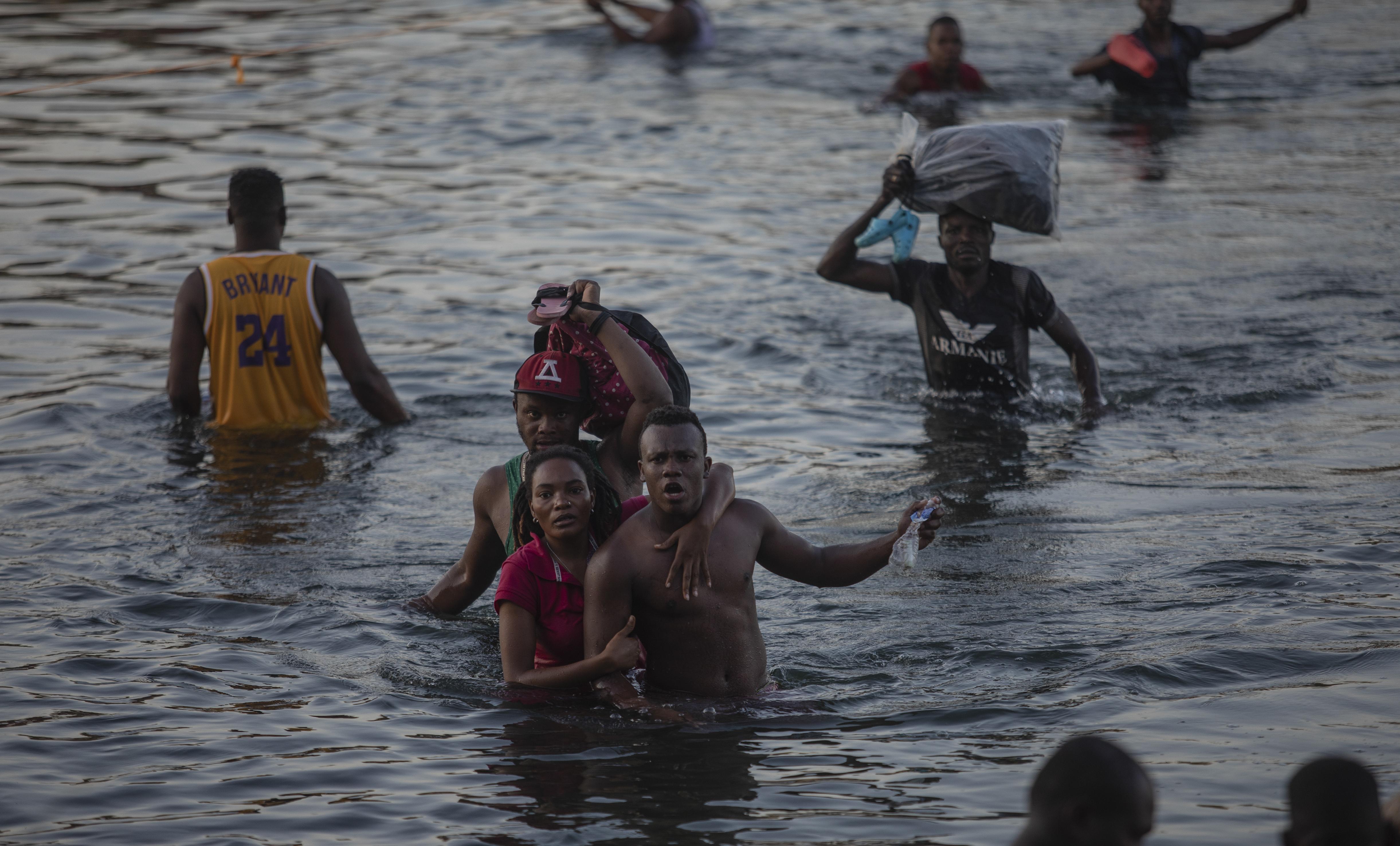 Haitian migrants wade across the Rio Grande to escape deportation.