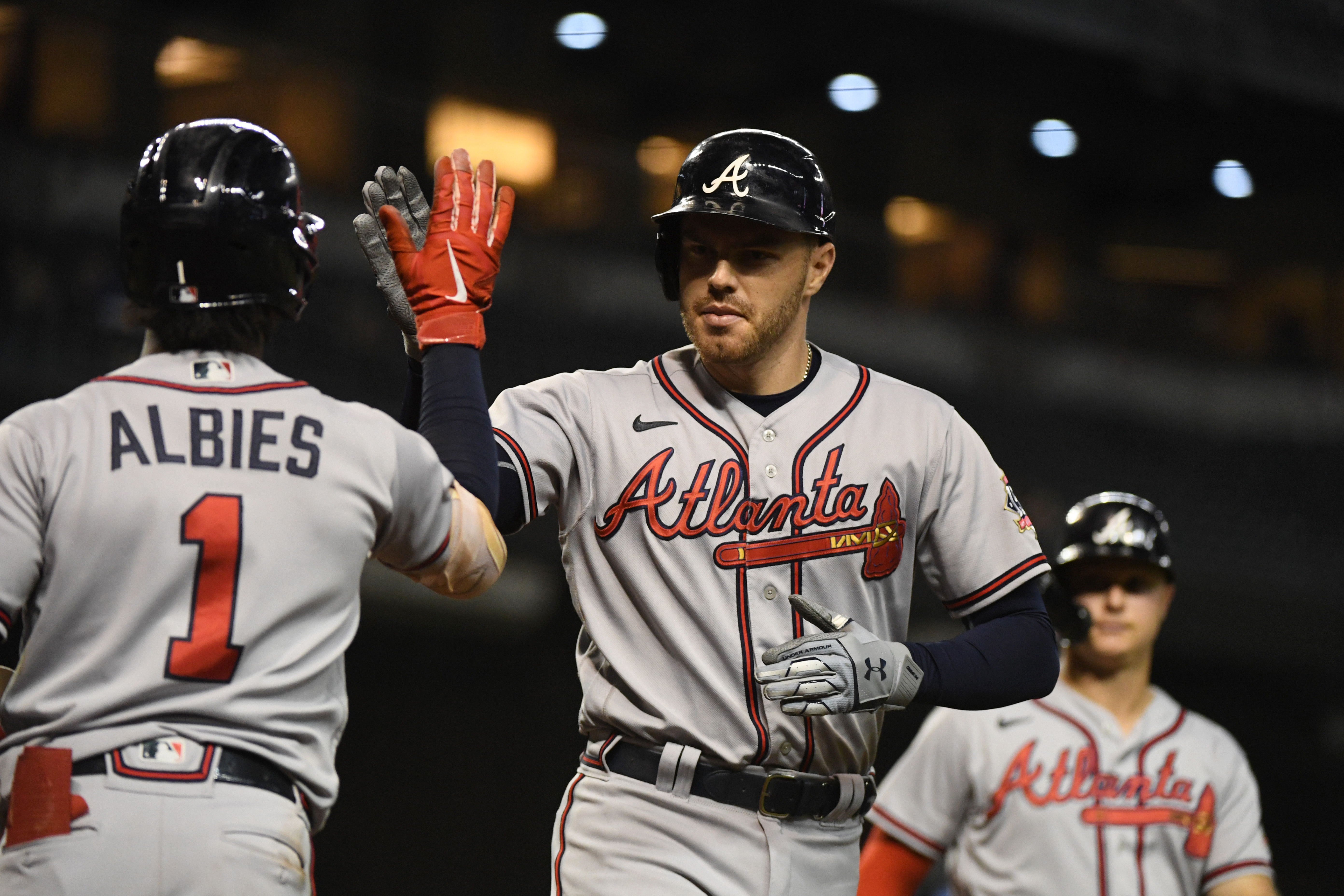 Freddie Freeman #5 of the Atlanta Braves celebrates with Ozzie Albies #1 after hitting a two-run home run off Tyler Clippard #36 of the Arizona Diamondbacks during the ninth inning at Chase Field on September 22, 2021 in Phoenix, Arizona.
