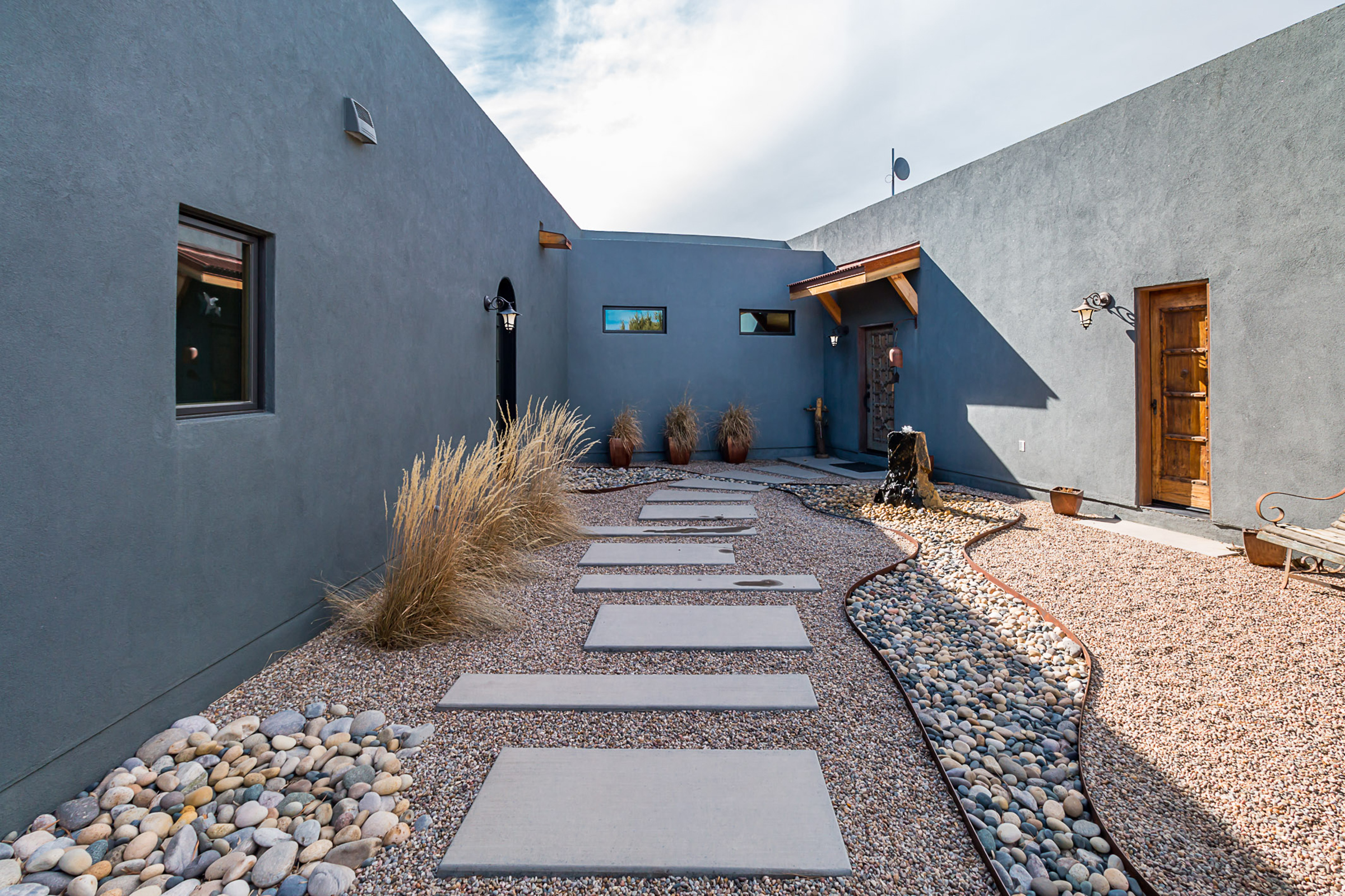 The courtyard of a southwestern home with a rock path