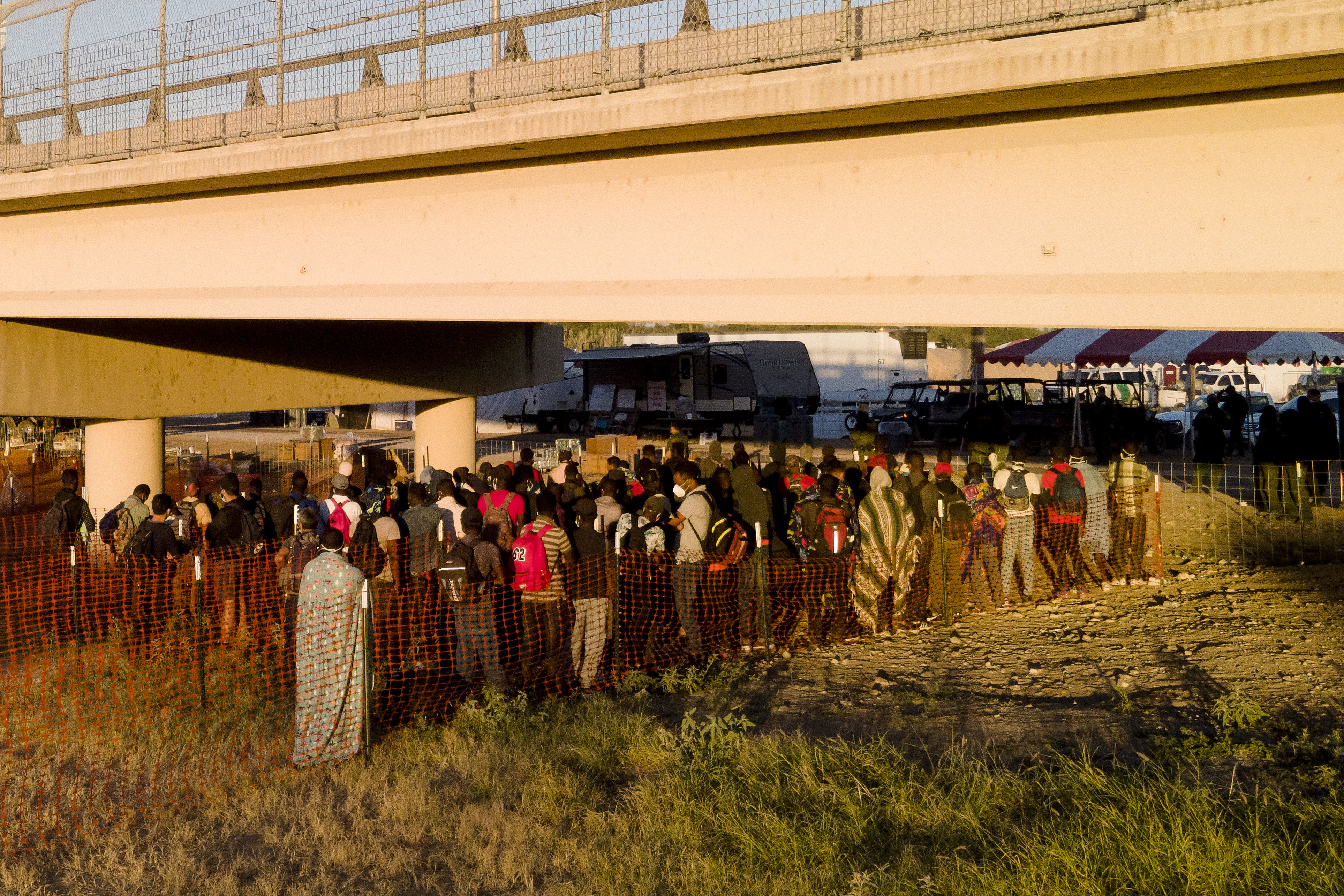 Migrants, many from Haiti, wait in lines to board buses under the Del Rio International Bridge, Friday, Sept. 24, 2021, in Del Rio, Texas.
