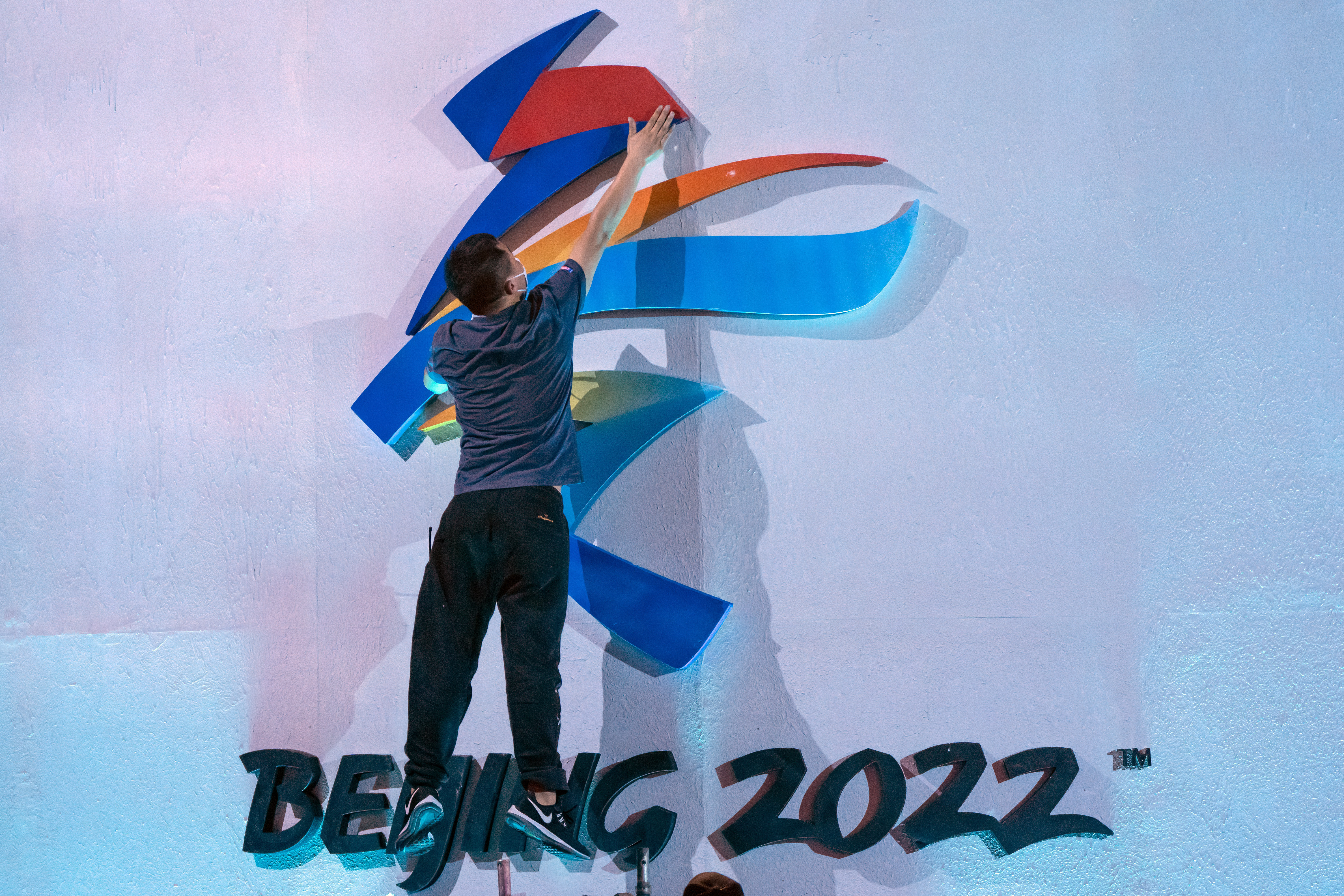 A crew member leaps to fix a logo for the 2022 Beijing Winter Olympics in Beijing on Friday, Sept. 17, 2021.
