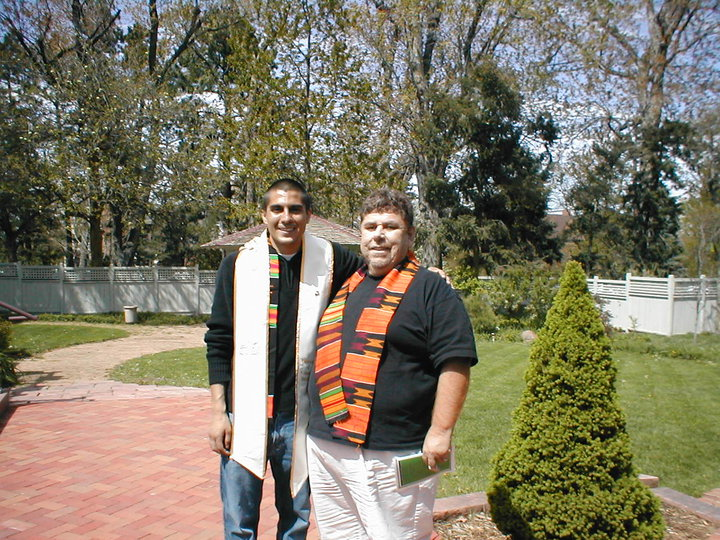 Two men dressed in black shirts and multi-colored graduation sashes stand in front of a courtyard with trees, a patio and grass.