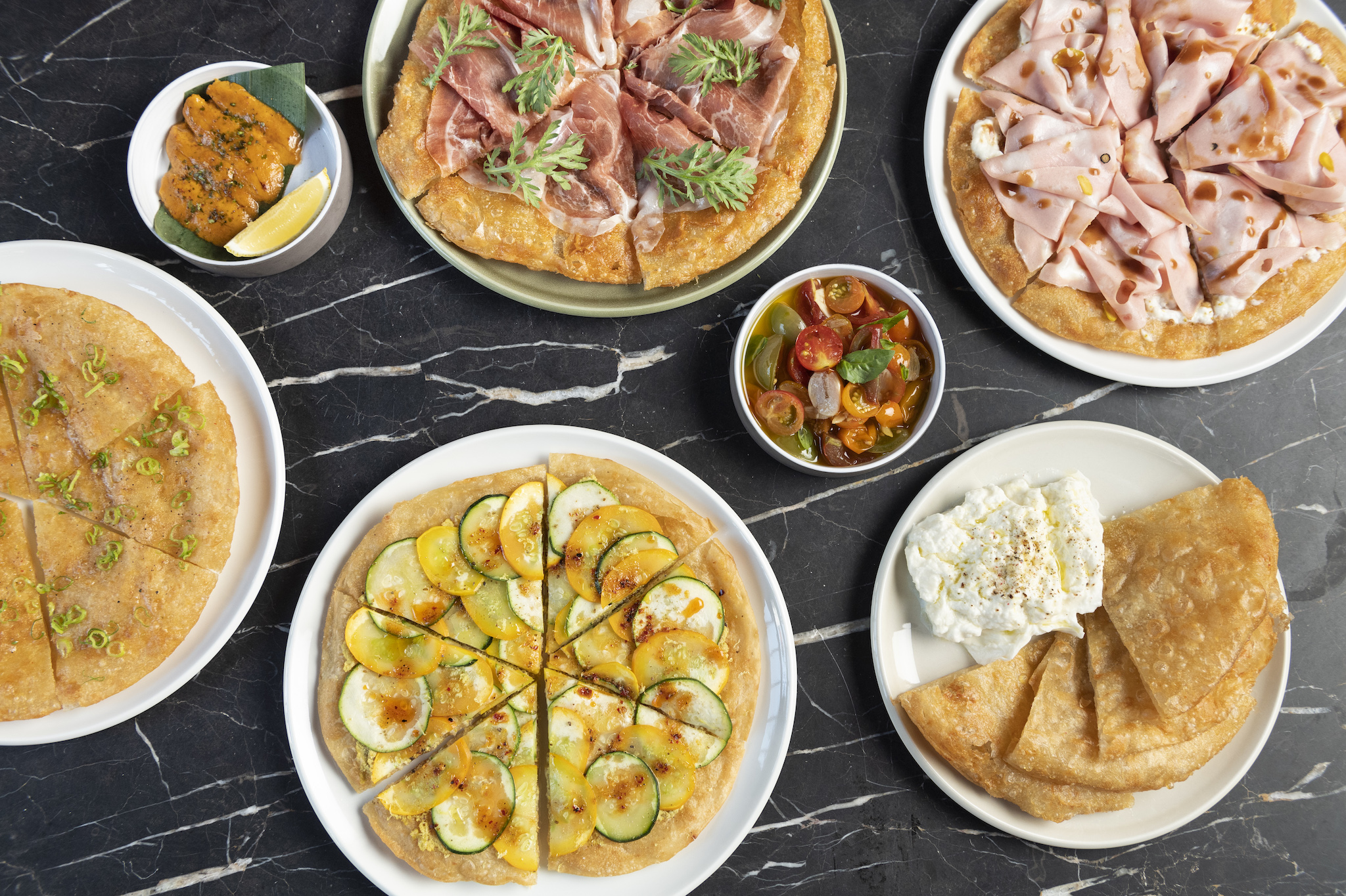 A spread of dishes with flatbreads topped with different items such as mortadella and zuchinni.