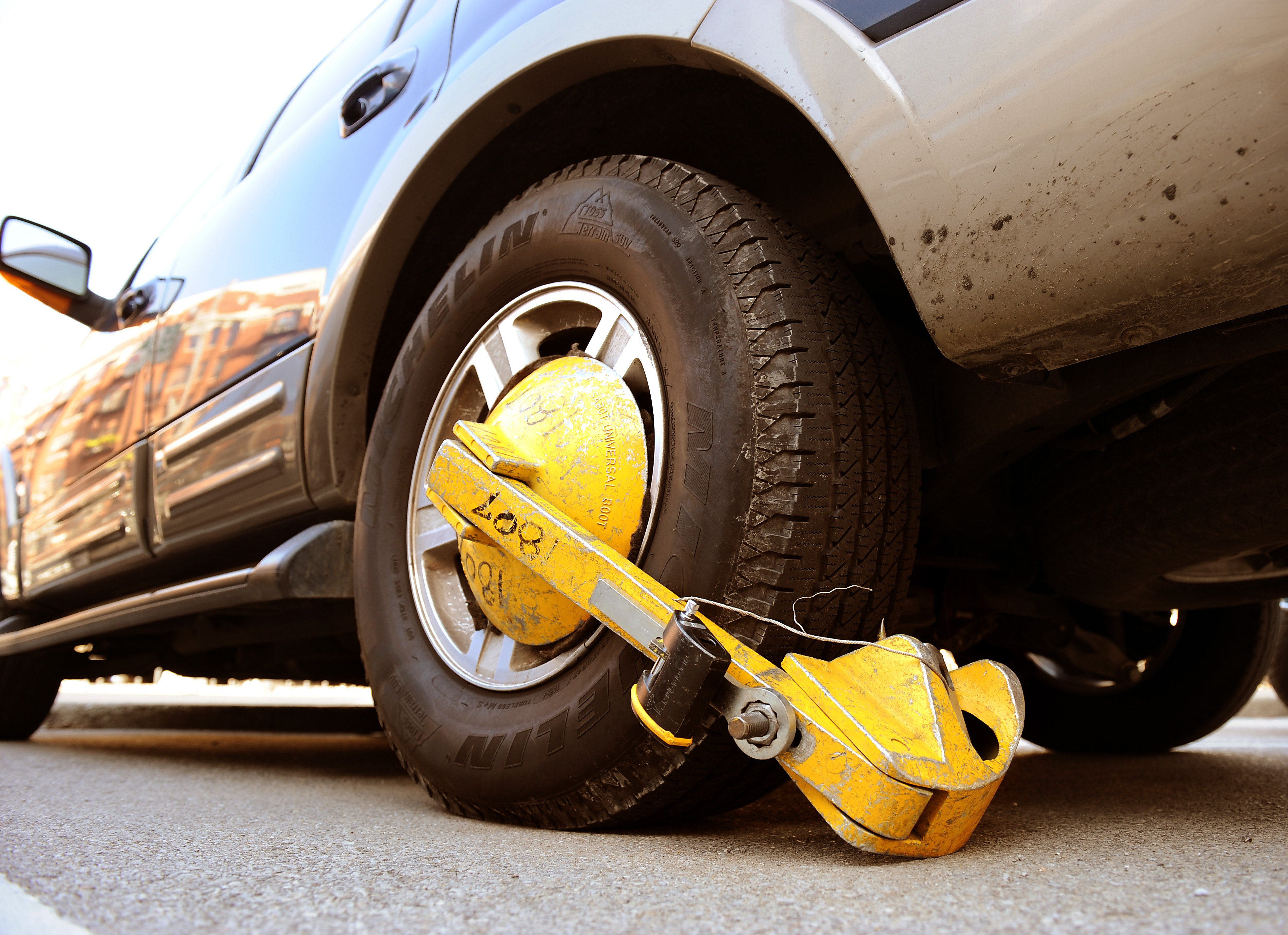 """The """"Denver Boot"""" is affixed to an automobile near the East Bank Club."""