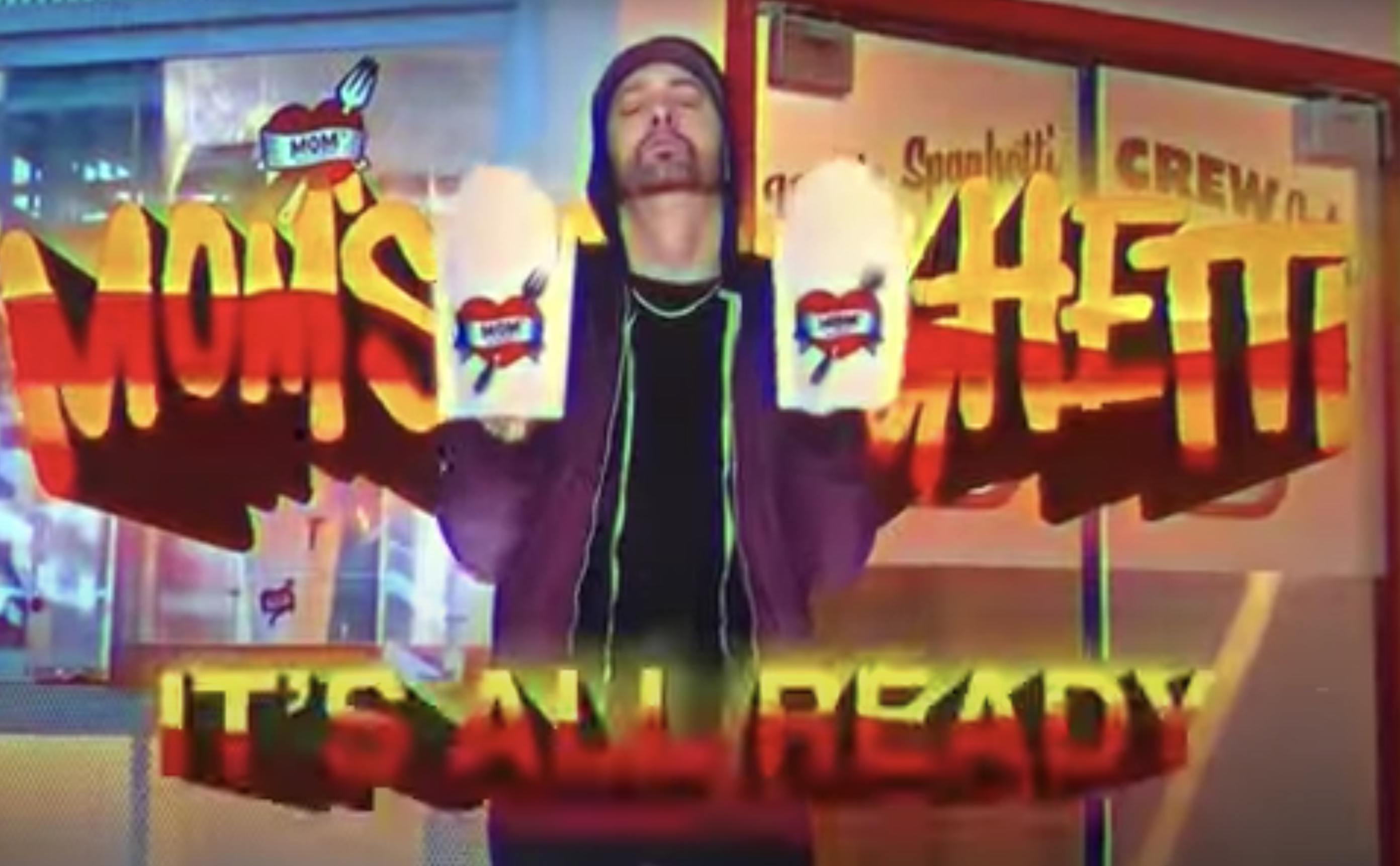 A screen grab of the television commercial shows Eminem in front of the Detroit skyline holding cartons of spaghetti.