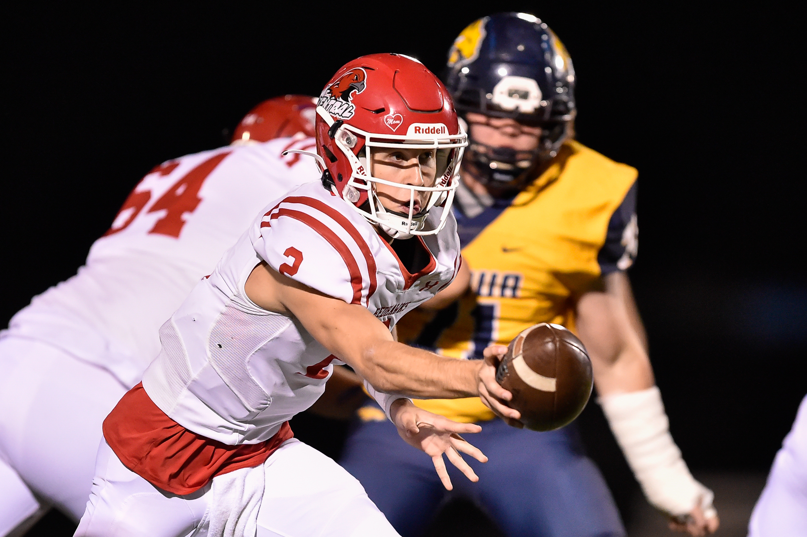 Naperville Central's Owen Prucha (2) hands off the ball against Neuqua Valley.