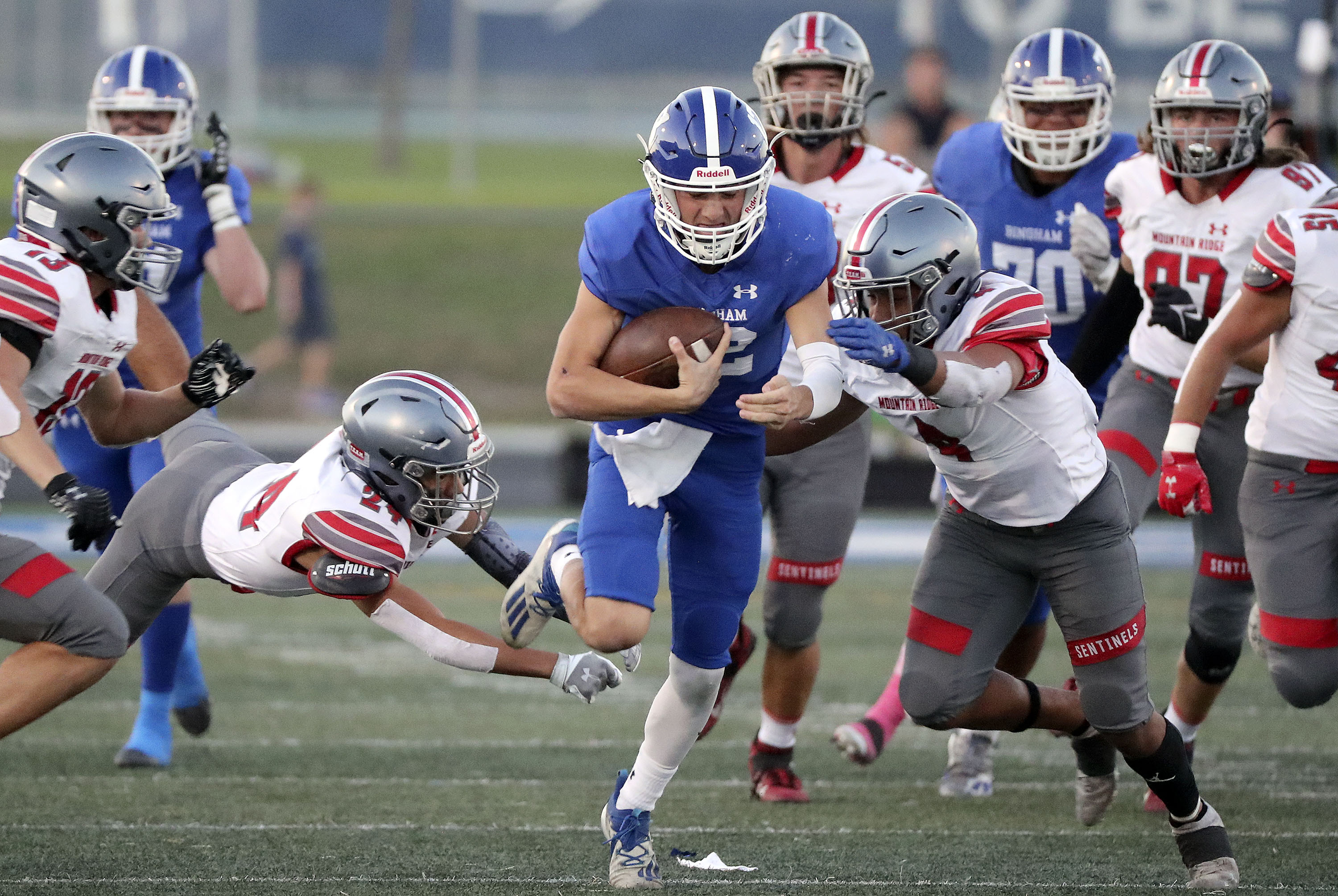 Bingham's Dallen Martinez gets tackled by Mountain Ridge's Chase Leiataua (24) and DeMarco Brimmage (4)