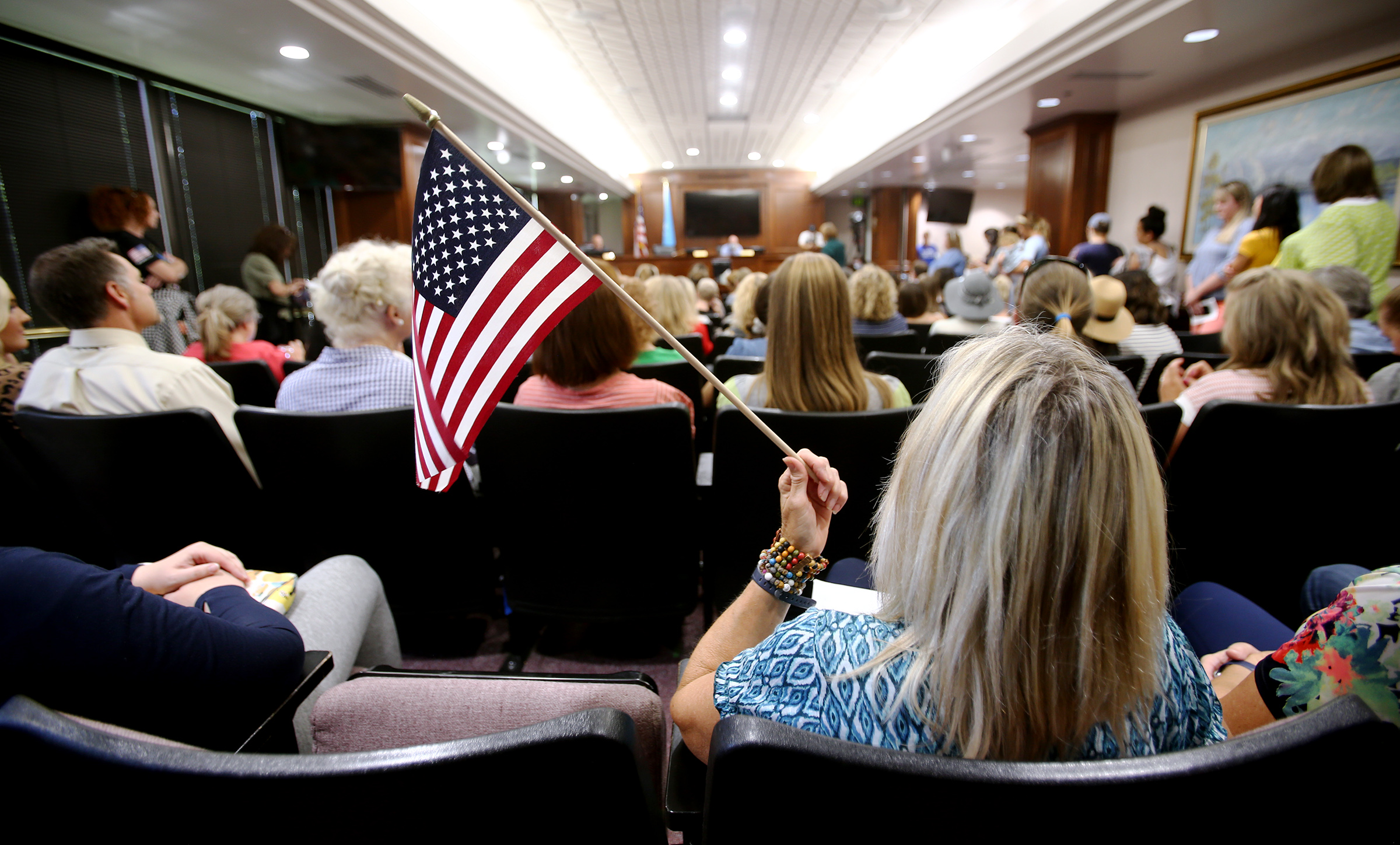A woman holds an American flag during a Utah County Commission meeting.