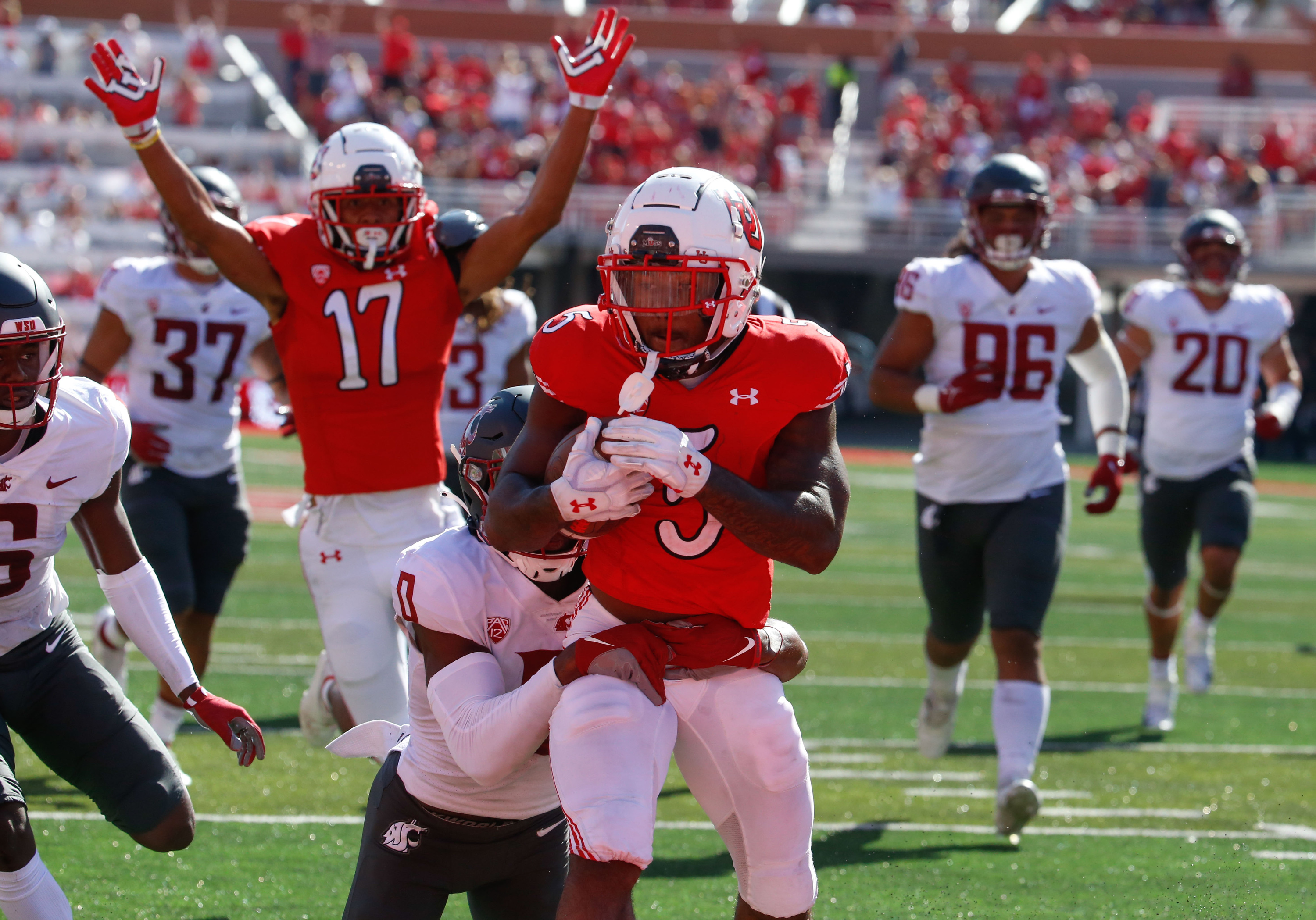 Utah running back TJ Pledger, center, gets tackled by Washington State defensive back Jaylen Watson as others celebrates during touchdown of an NCAA college football game at Rice-Eccles Stadium on Saturday, Sept. 25, 2021 in Salt Lake City. Utah won the game 24-13.