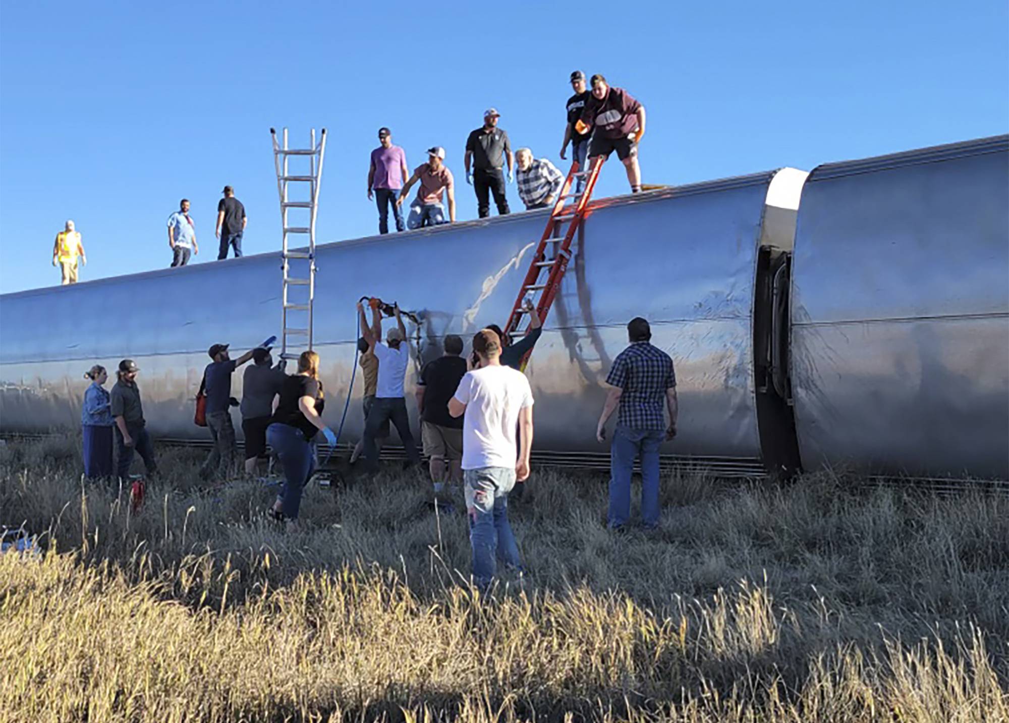 In this photo provided by Kimberly Fossen people work at the scene of an Amtrak train derailment on Saturday, in north-central Montana. Multiple people were injured when the train that runs between Seattle and Chicago derailed Saturday, the train agency said.