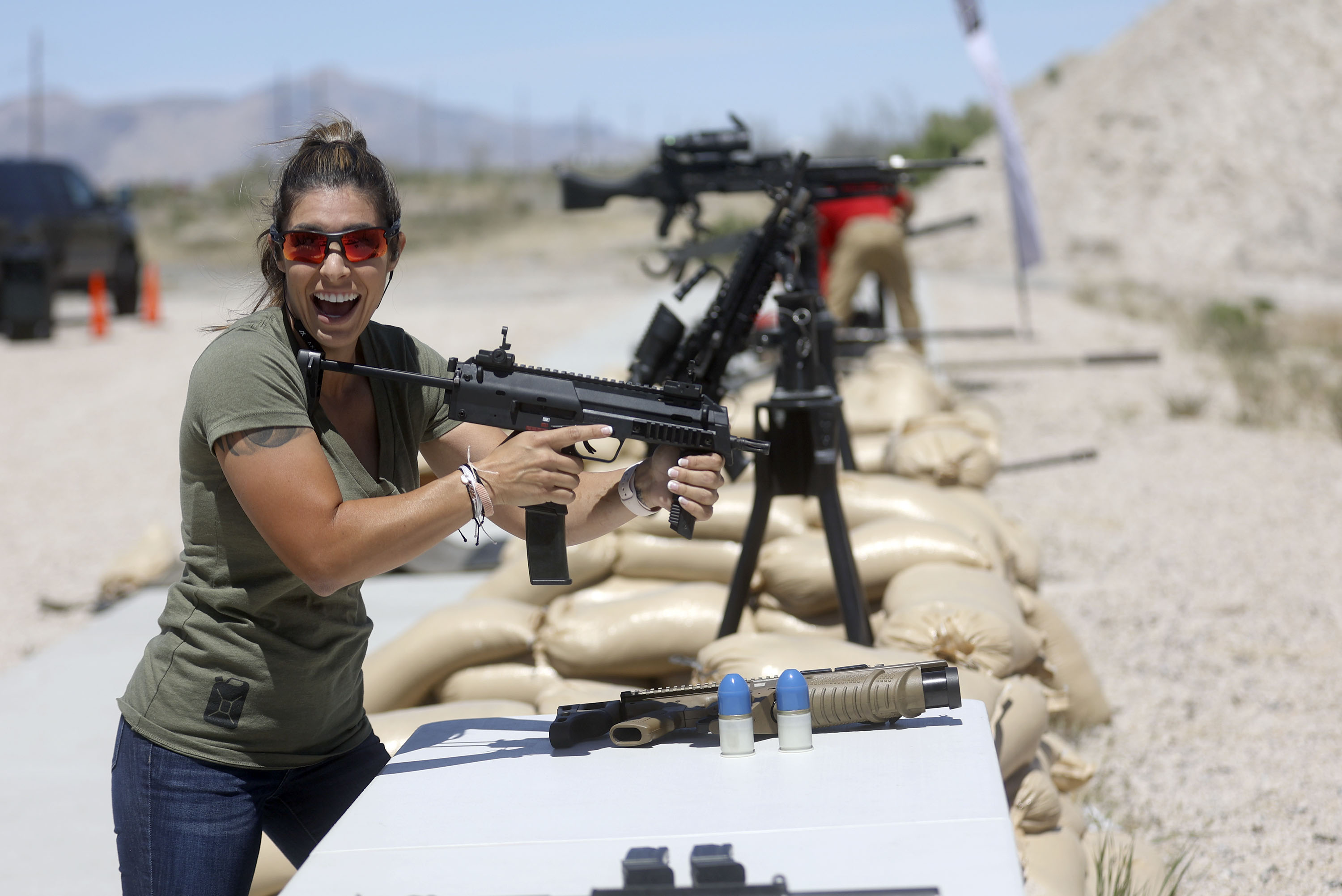 Michelle Viscusi reacts after firing a Heckler & Koch MP7 during the filming of a promotional video for a TacGas client.