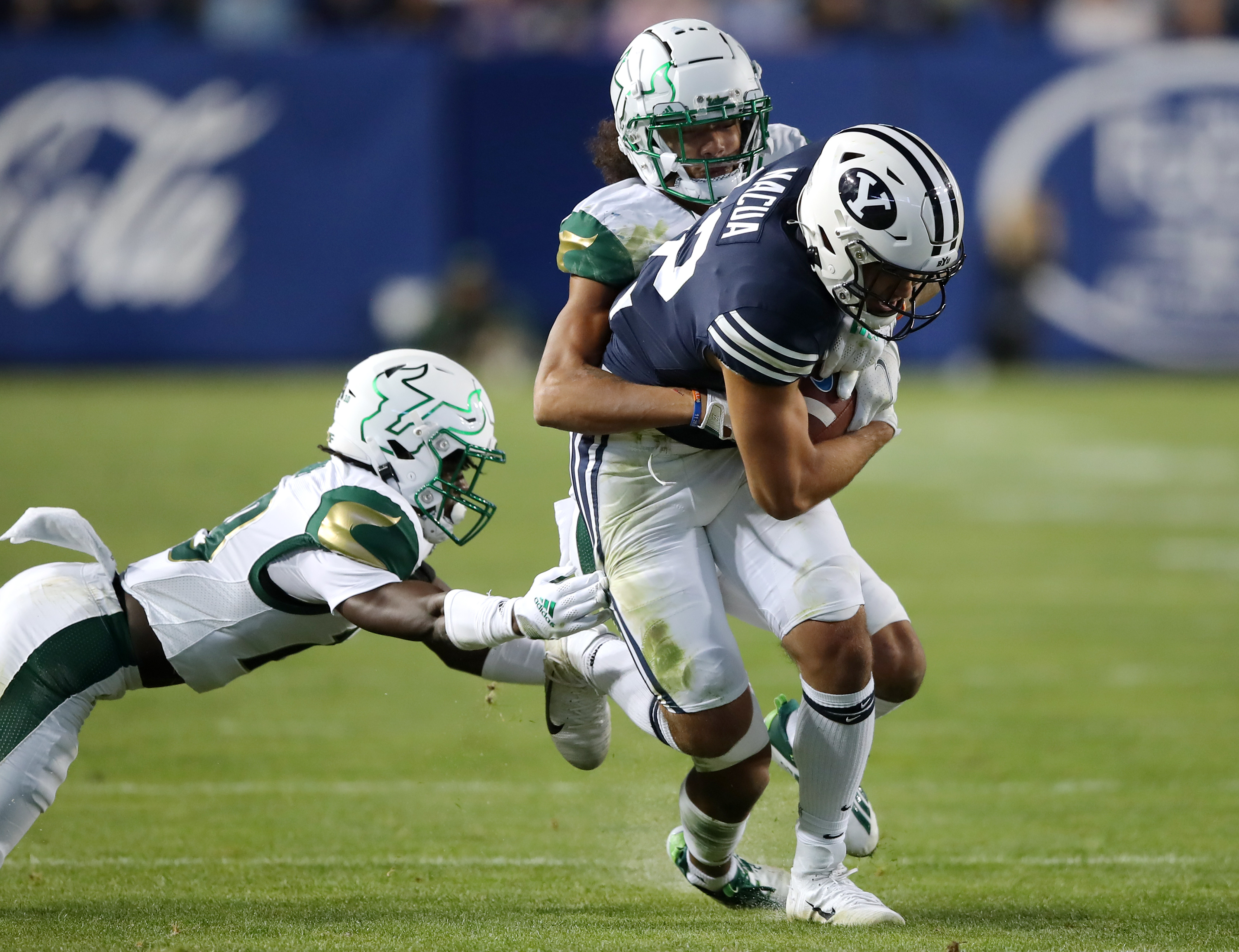 Brigham Young Cougars wide receiver Puka Nacua (12) is tackled after a catch and short run by South Florida Bulls defensive back Jalen Herring (19) and South Florida Bulls safety Matthew Hill (1) as BYU and USF play a college football game at LaVell Edwards Stadium in Provo on Saturday, Sept. 25, 2021. BYU won 35-27.