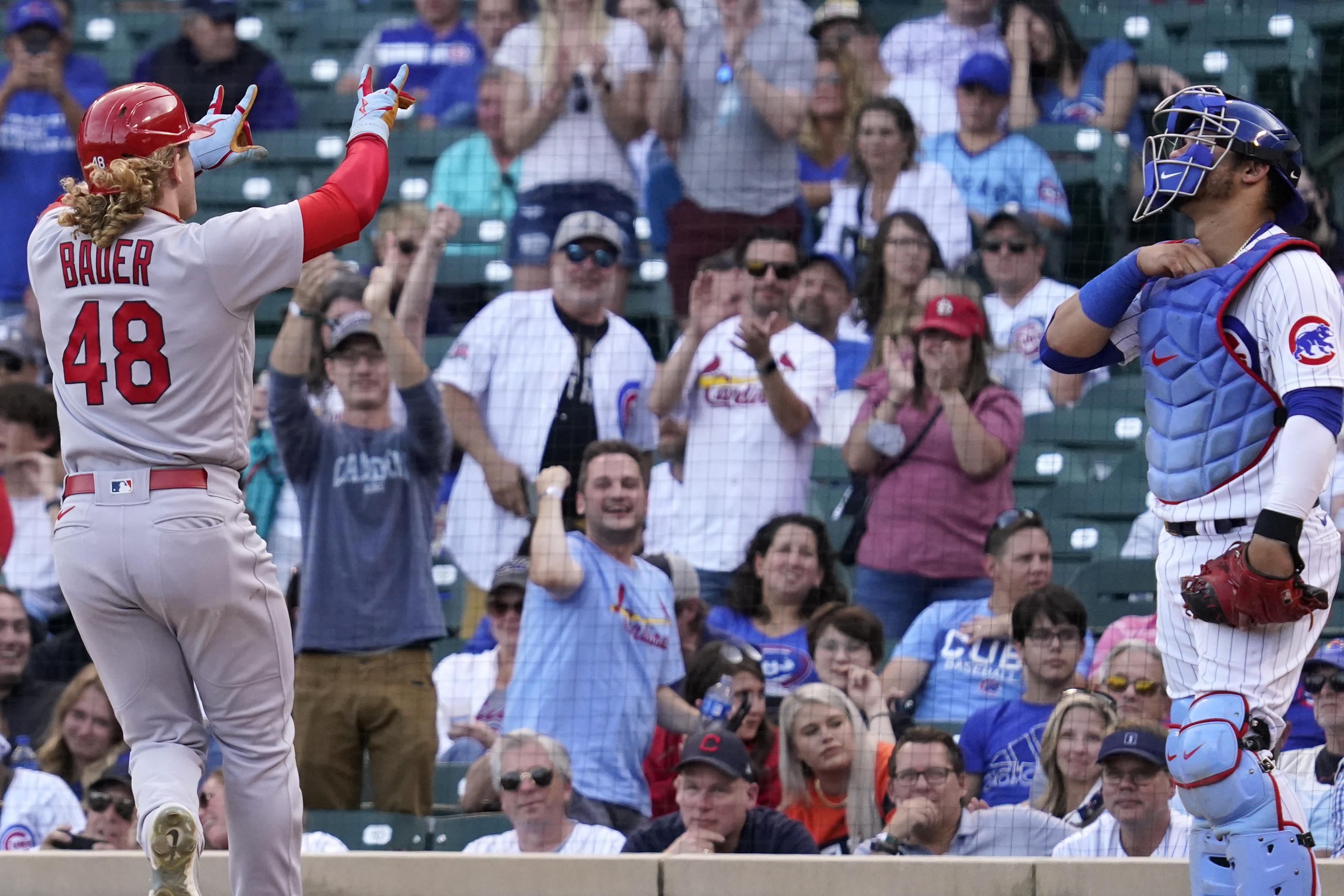 The Cardinals' Harrison Bader, left, celebrates after hitting a solo home run as Cubs catcher Willson Contreras looks on during the eighth inning of Sunday's game.