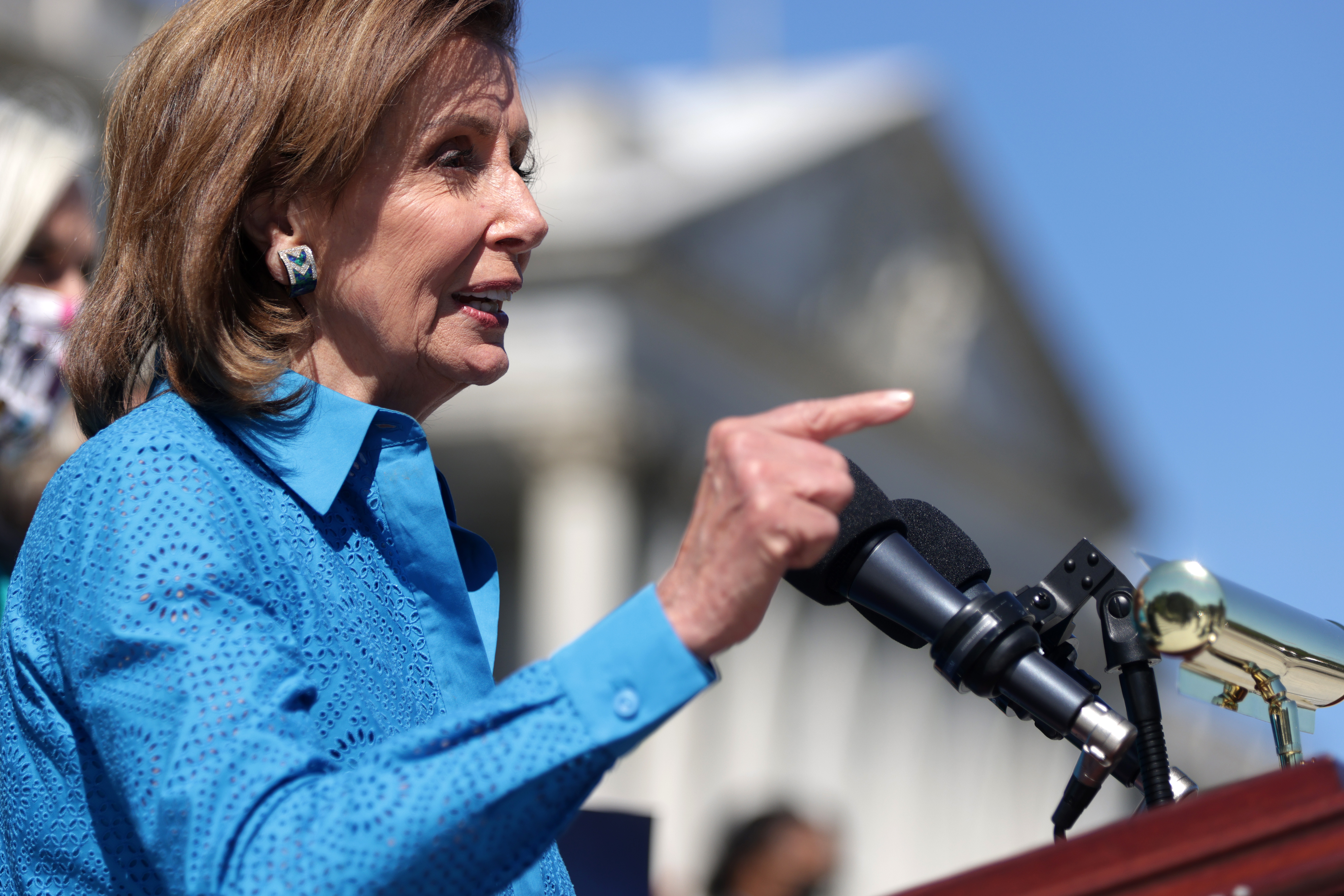 Speaker Nancy Pelosi gestures from behind a podium while speaking outside of the US Capitol.