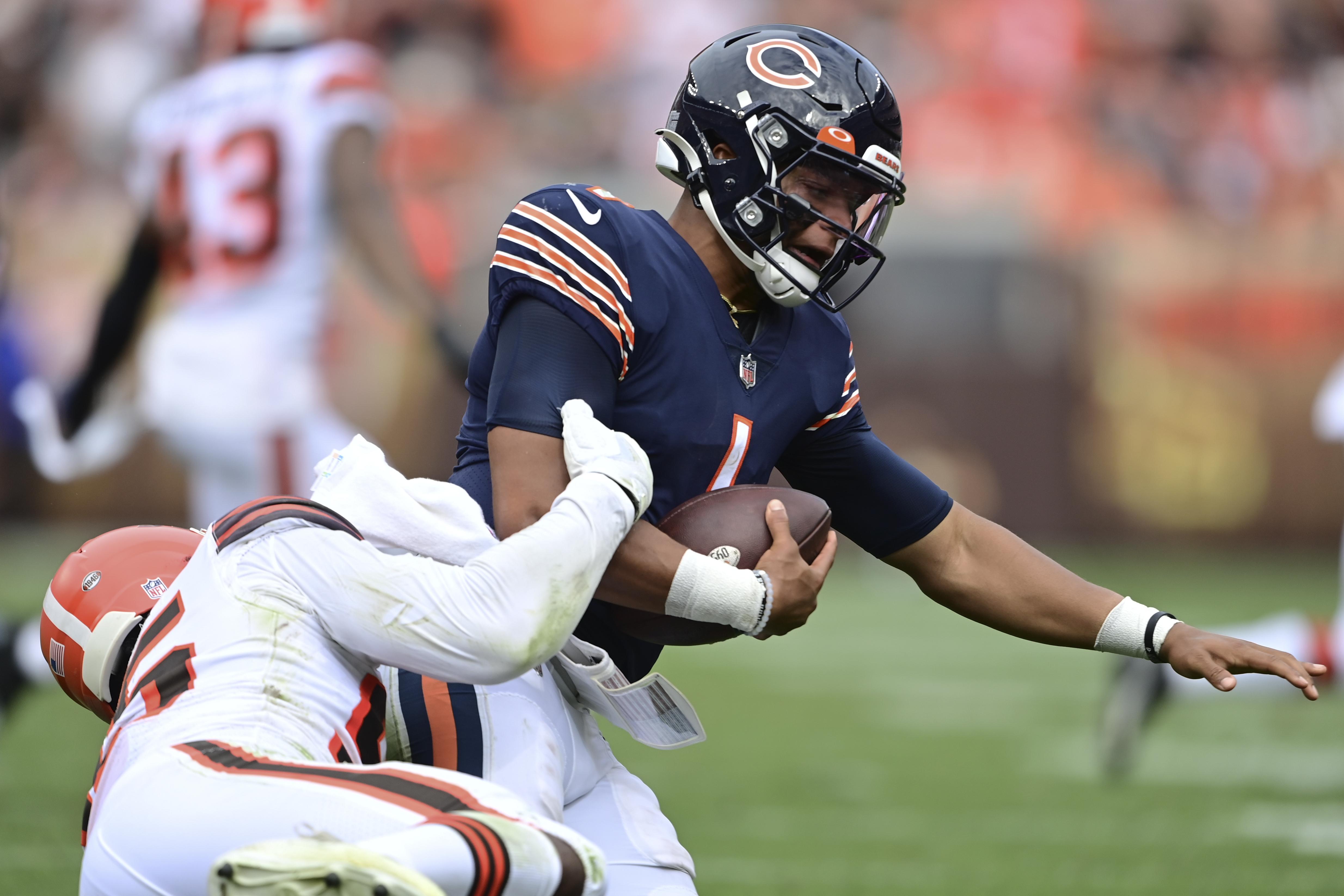 Browns defensive end Myles Garrett, left, makes one of his 4.5 sacks against Bears quarterback Justin Fields.