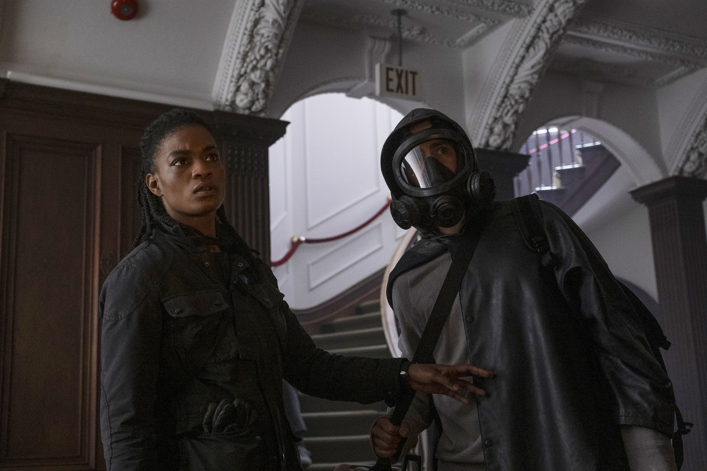 Agent 355 and Yorick (in a mask) look  in concern at something just off-camera.