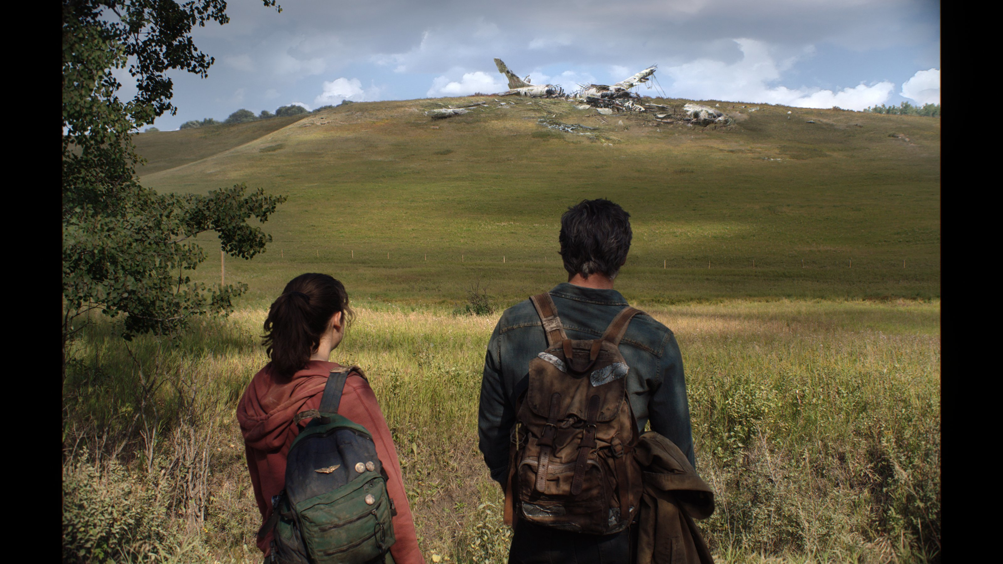 Joel and Ellie stare at a downed airplane in The Last of Us TV series