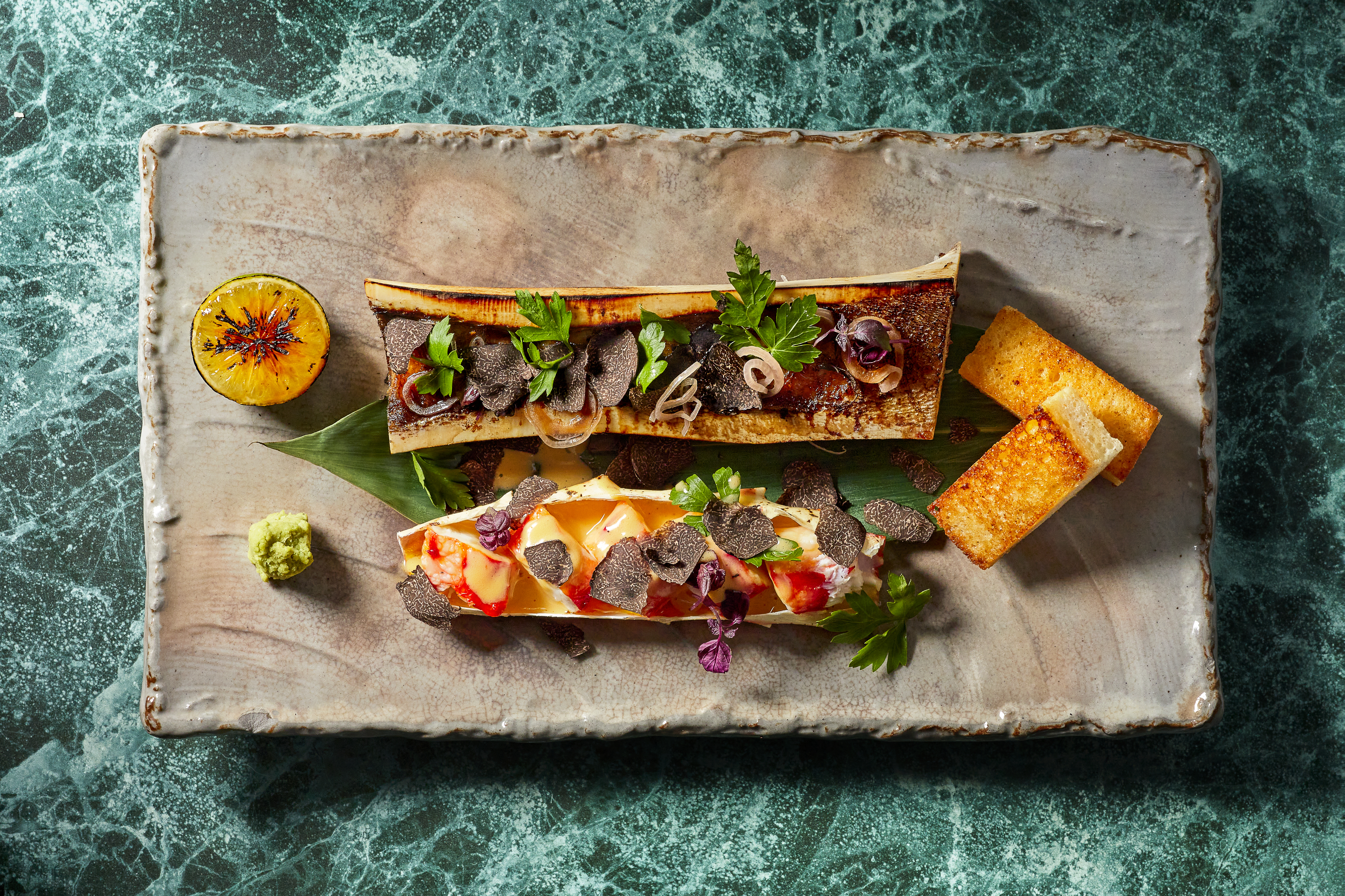 two pieces of bone marrow with colorful toppings on a piece of slate with a blue background