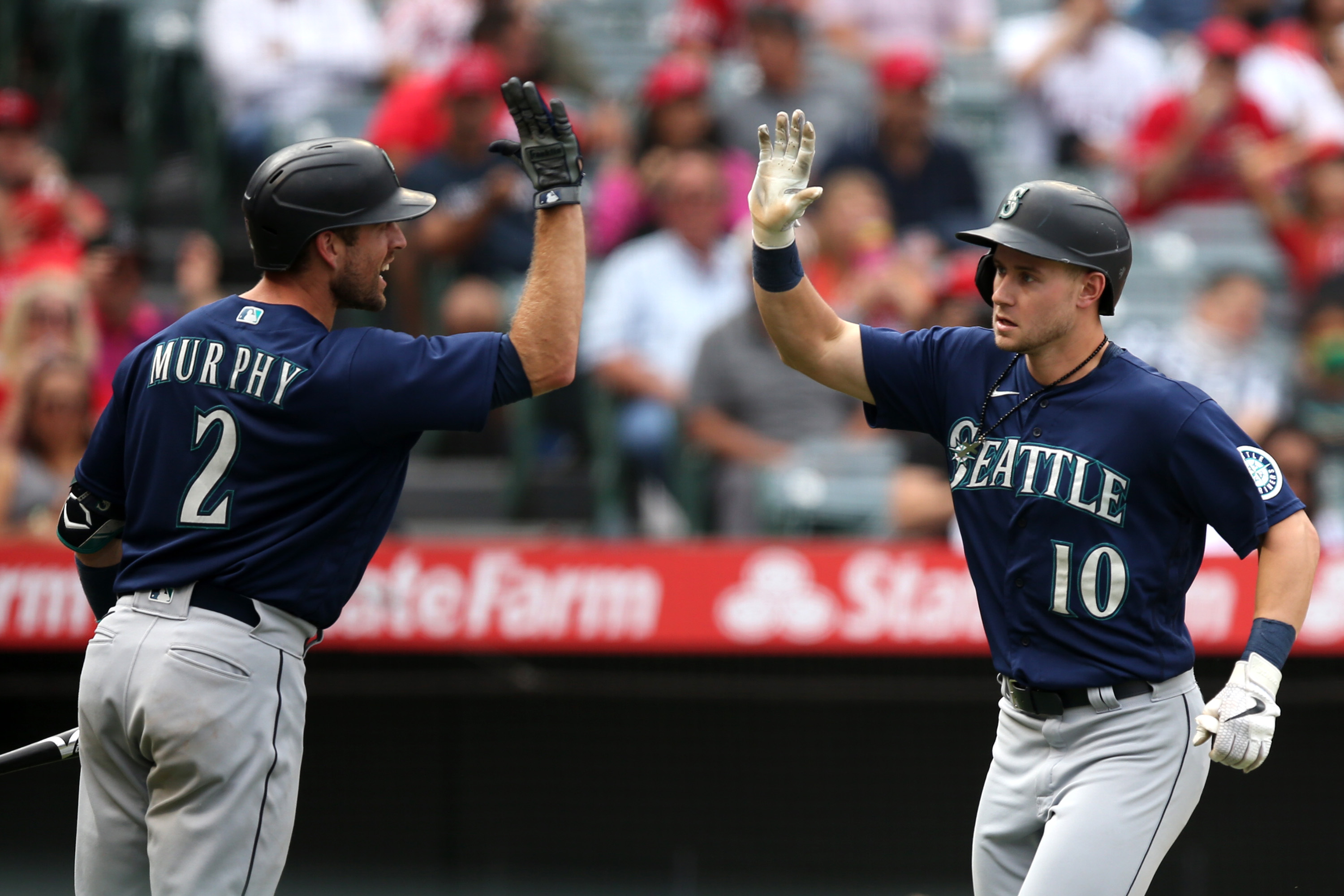 Tom Murphy #2 of the Seattle Mariners high-fives Jarred Kelenic #10 of the Seattle Mariners after Kelenic hit a home run in the seventh inning against the Los Angeles Angels at Angel Stadium of Anaheim on September 26, 2021 in Anaheim, California.