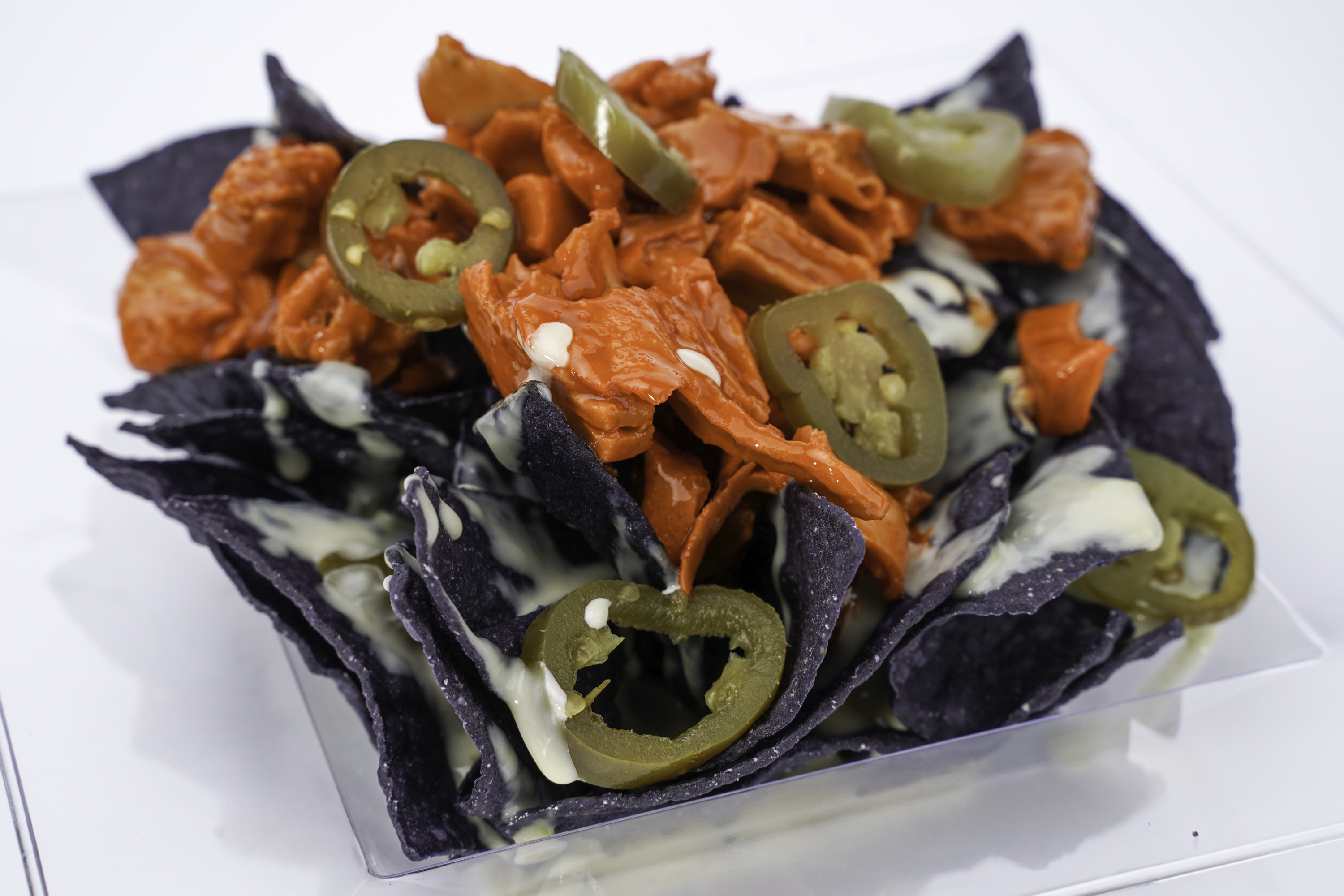 Blue corn tortilla chips topped with cheese, buffalo chicken, and pickled jalapenos