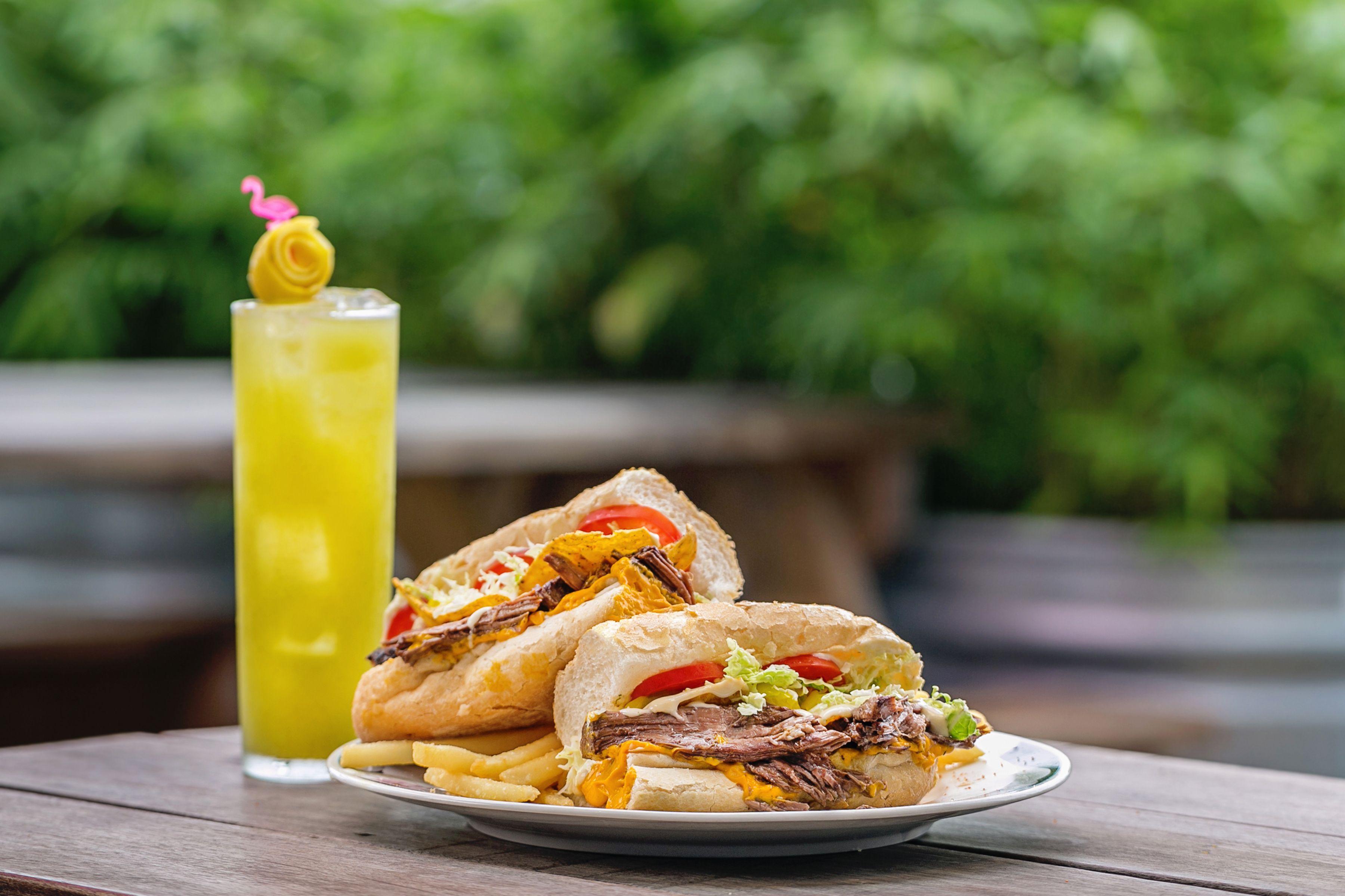 a beefy po'boy sandwich and a yellow cocktail with a lemon twist