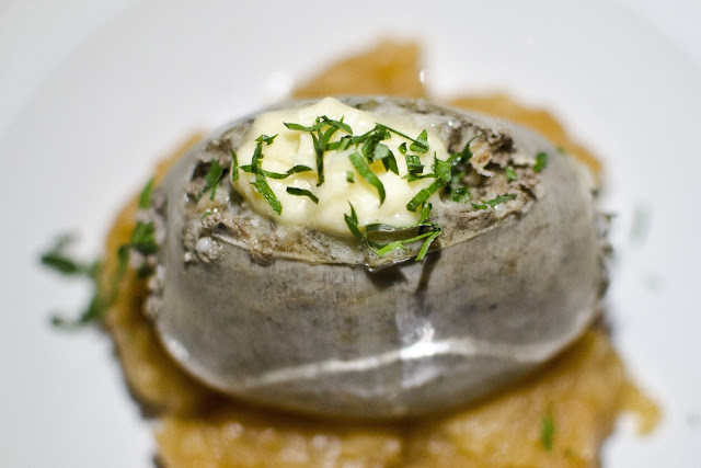 A portion of haggis sits on a bed of mashed rutabaga, garnished with Drambuie butter