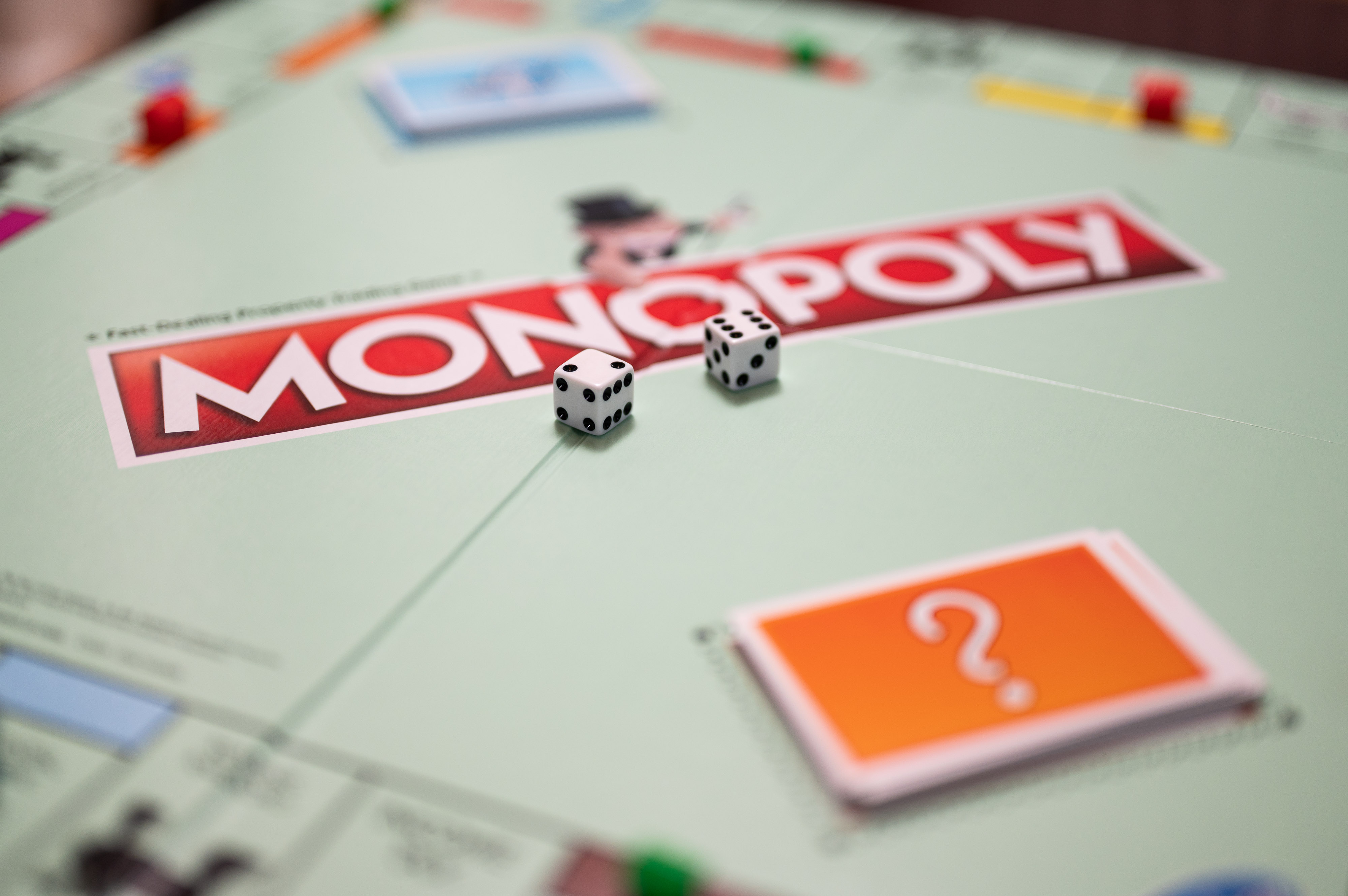 Two six-sided dice sit at the center of a Monopoly board.