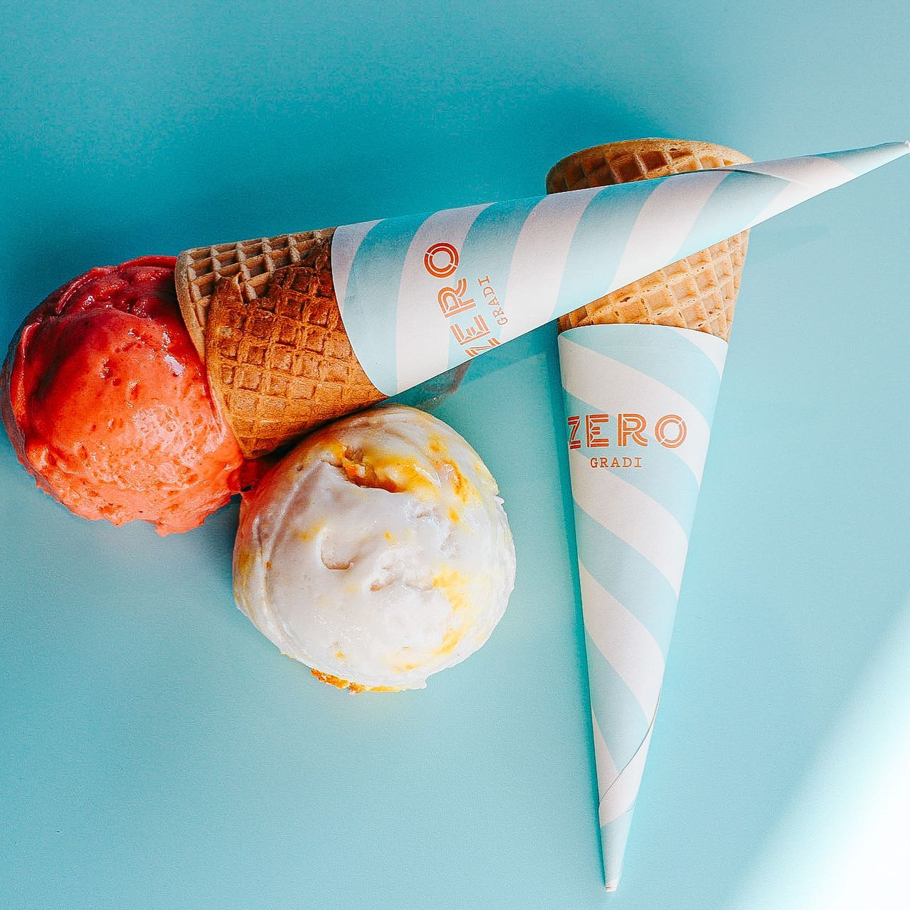 two scoops of gelato with two waffle cones on a blue background