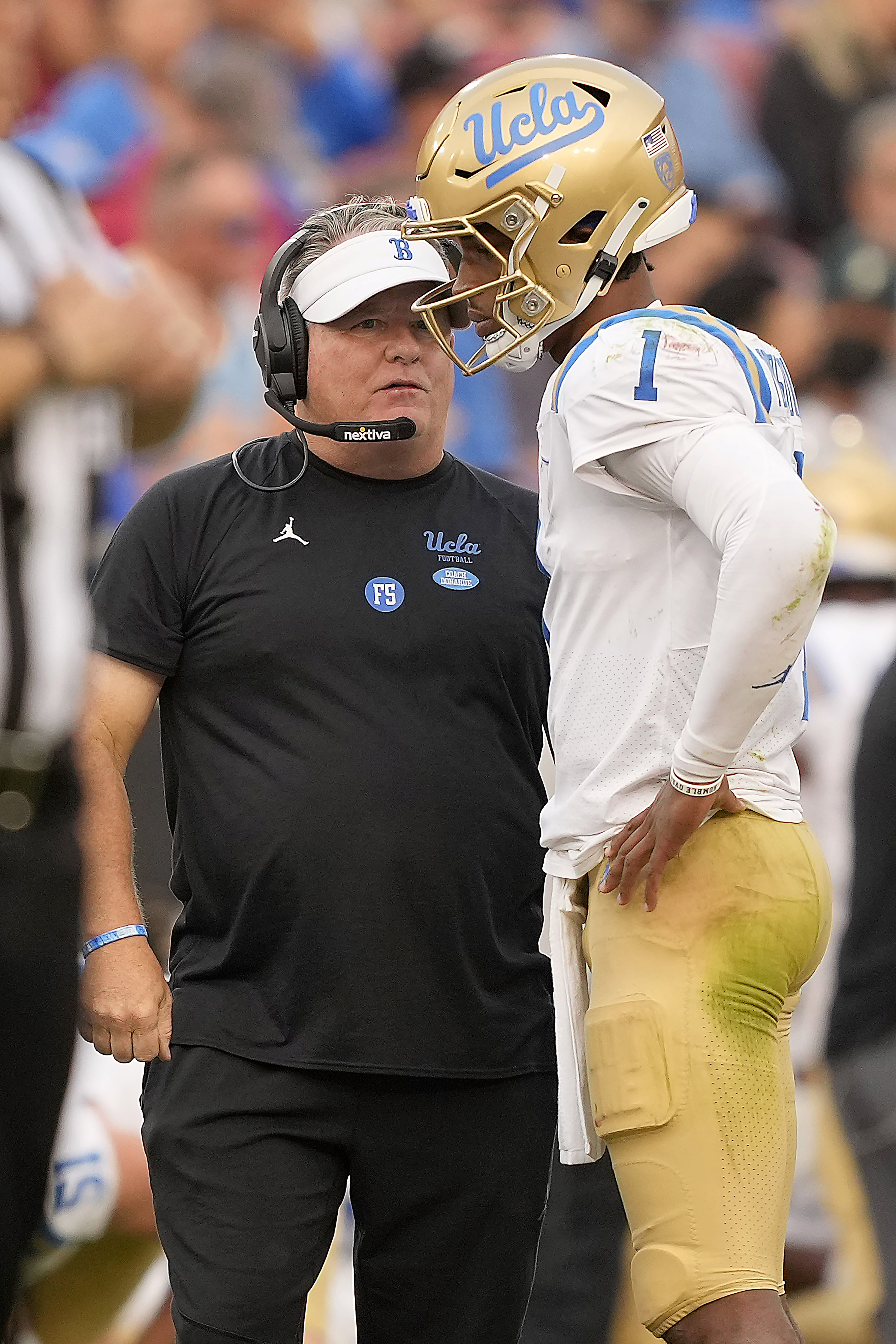 UCLA coach Chip Kelly, left, talks to quarterback quarterback Dorian Thompson-Robinson (1) during a game against Stanford Saturday.