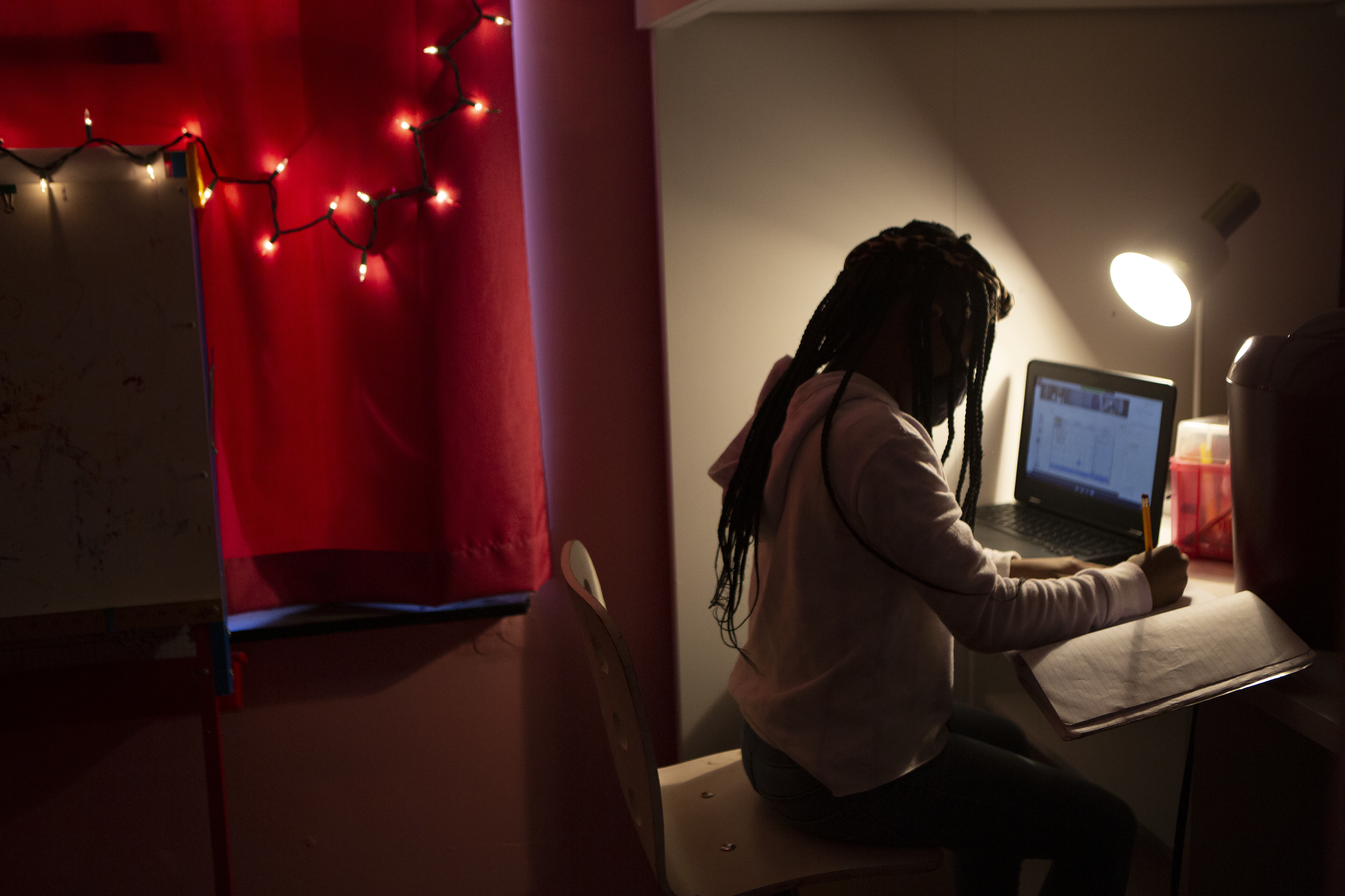 A young girl in a darkened room works in the light of a desk lamp. She is writing in a notebook. A laptop computer is open on her left. Behind her a string of Christmas lights hang over a red curtain.