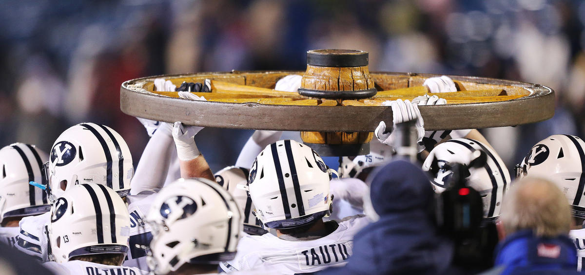 Brigham Young Cougars carry the Old Wagon Wheel after beating USU in Logan Saturday, Nov. 28, 2015. BYU won 51-28.