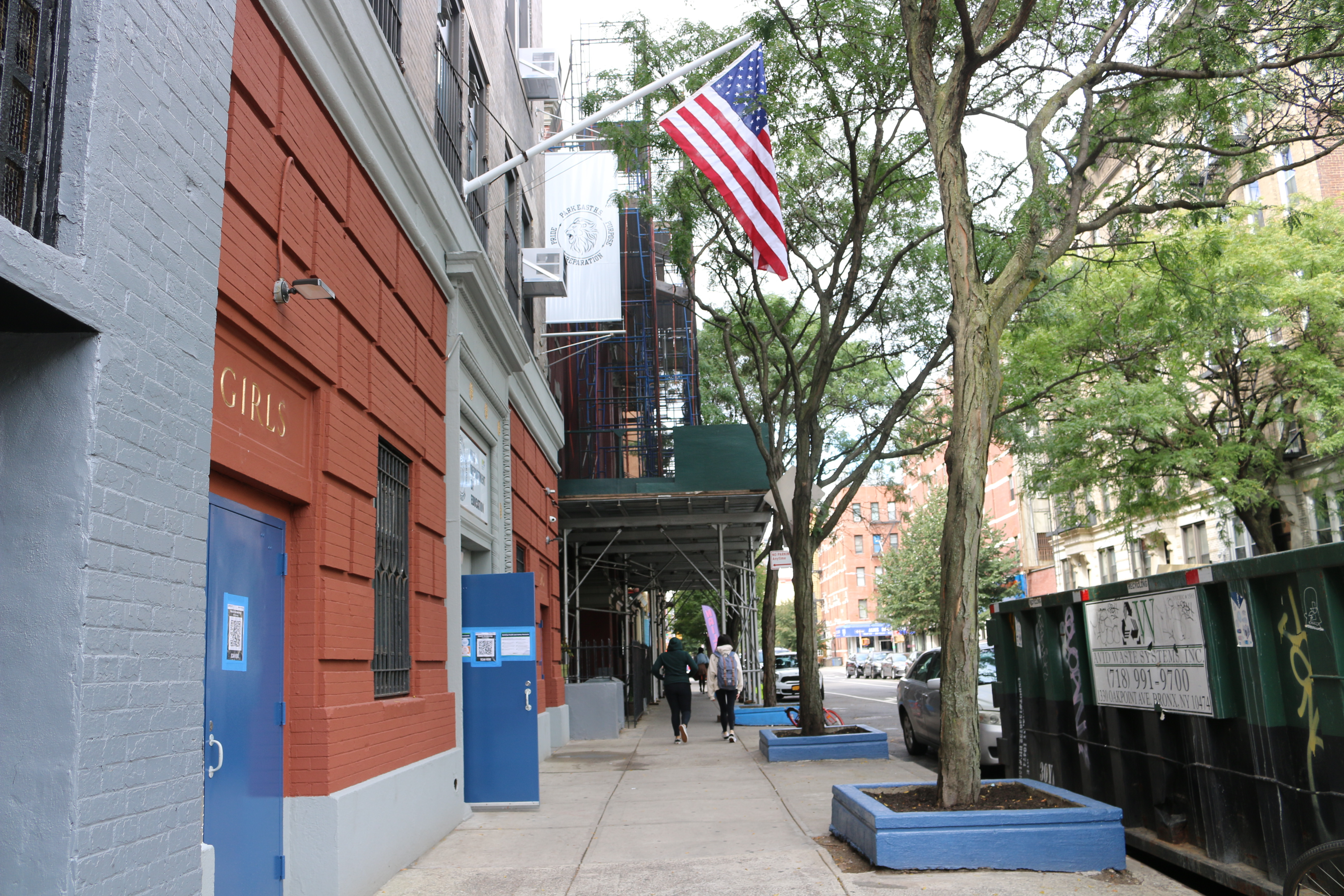 An American flag hangs above the entrance of a red brick building with blue doors.