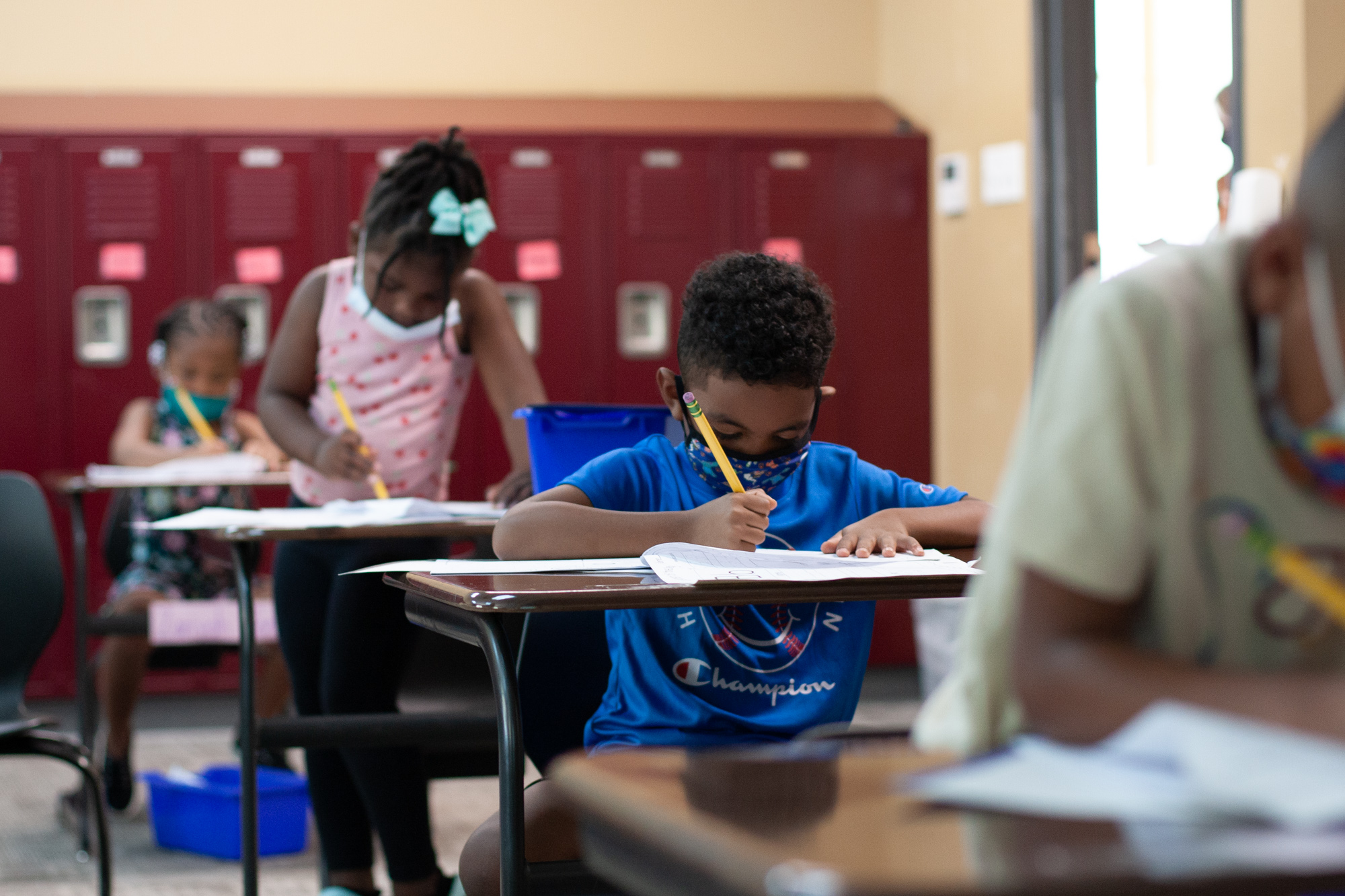 Four students sit in a row of desks in a classroom lined with red lockers. One boy wears a blue shirt and blue mask while writing on a worksheet