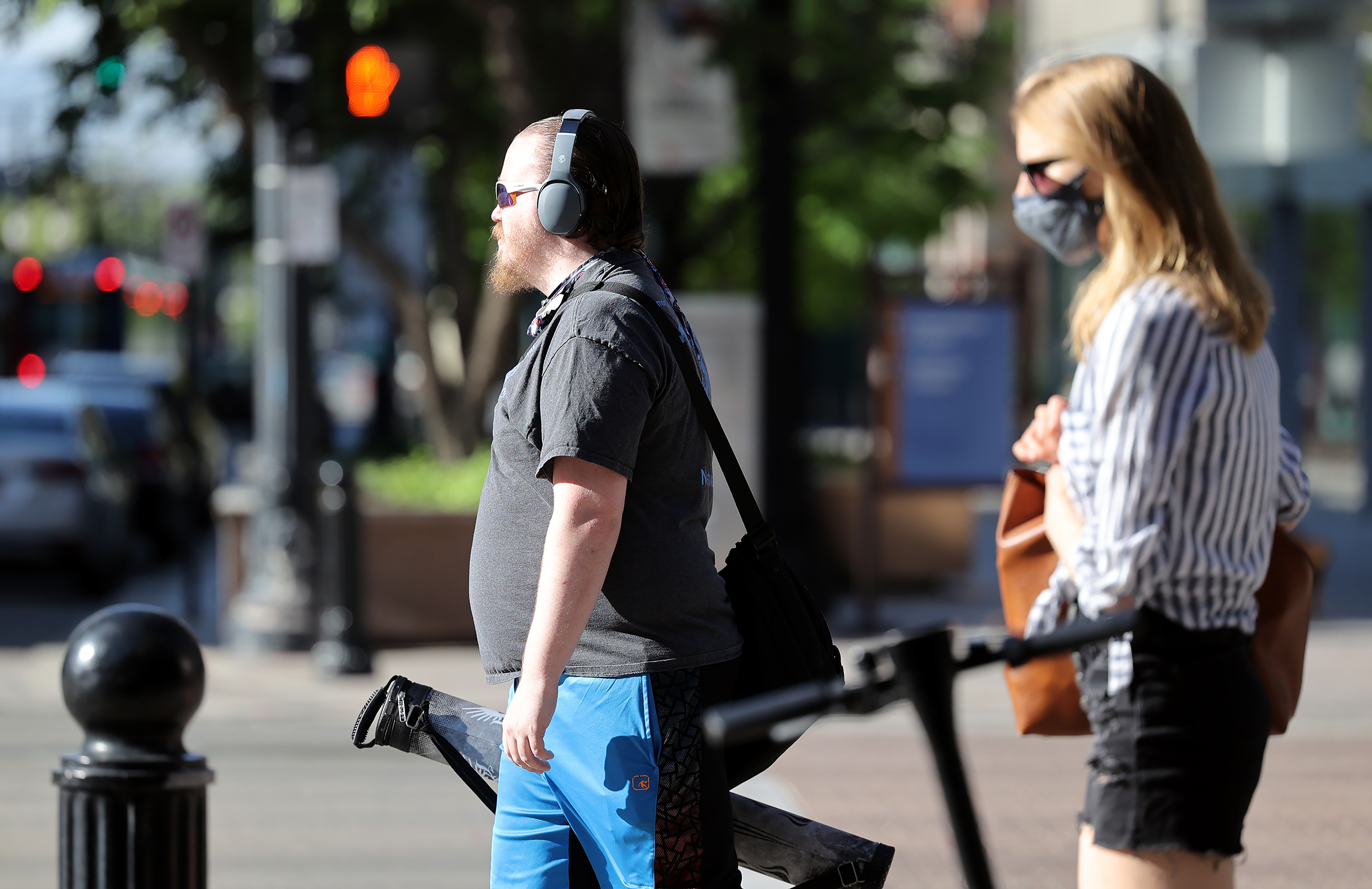 A maskless pedestrian and a pedestrian wearing a mask walk in Salt Lake City on Friday, May 14, 2021.