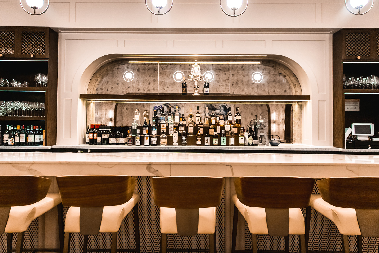 a marble bar with chairs and bottles of booze