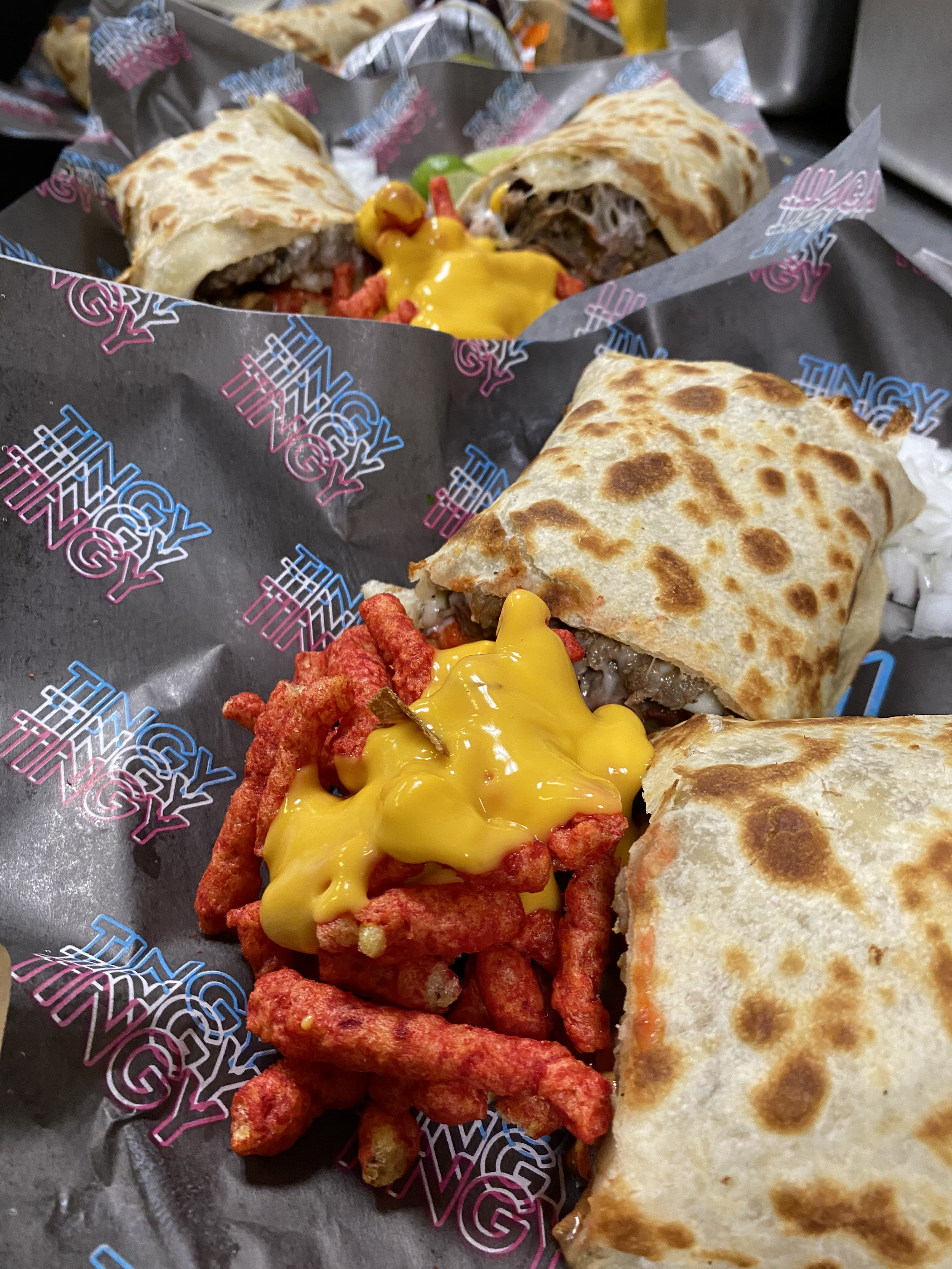 A pile of crunchy red Cheetos covered in yellow cheese next to burrito halves
