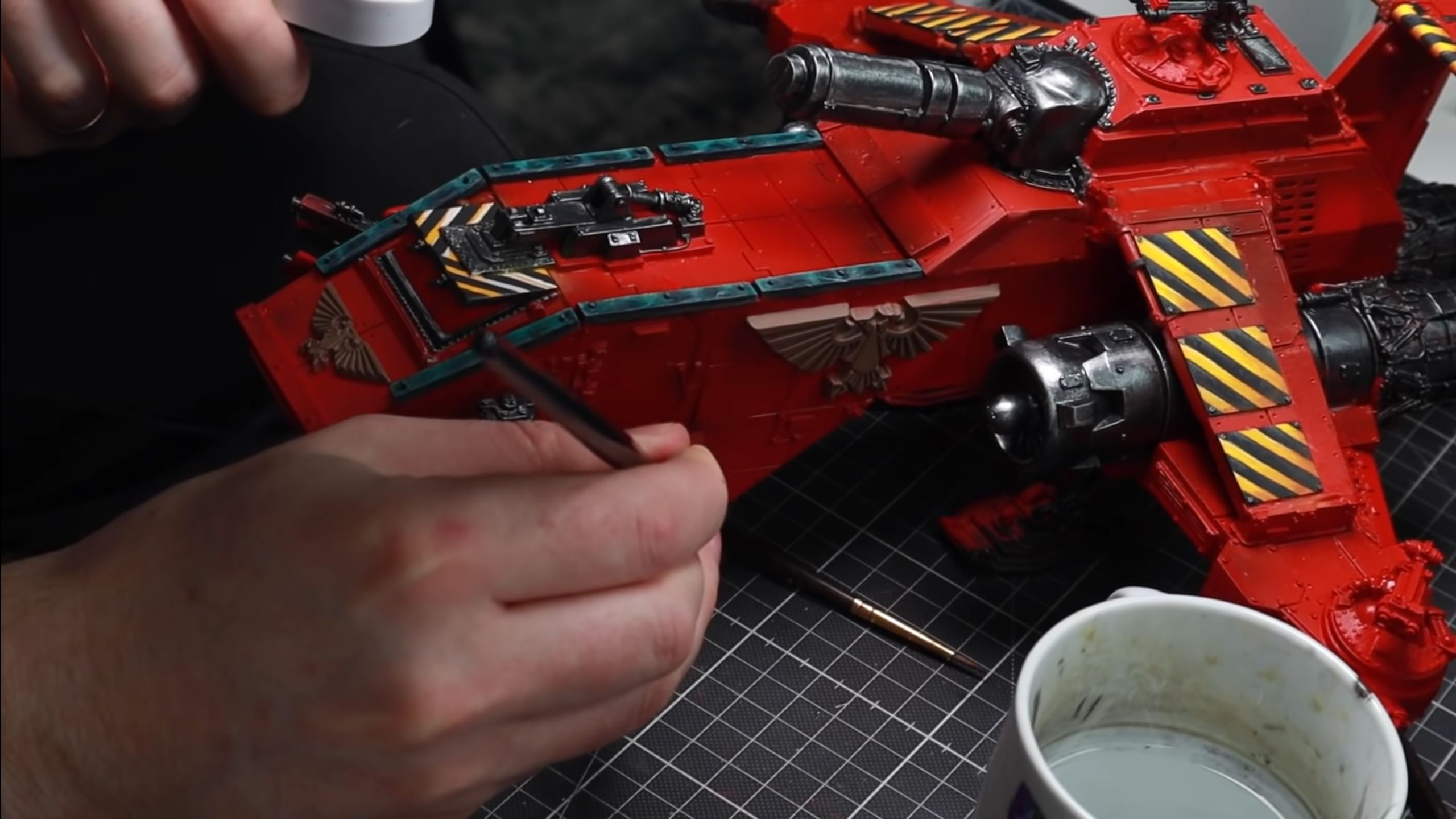 Emil paints fine highlights on the side of a Blood Angels Thunderhawk.