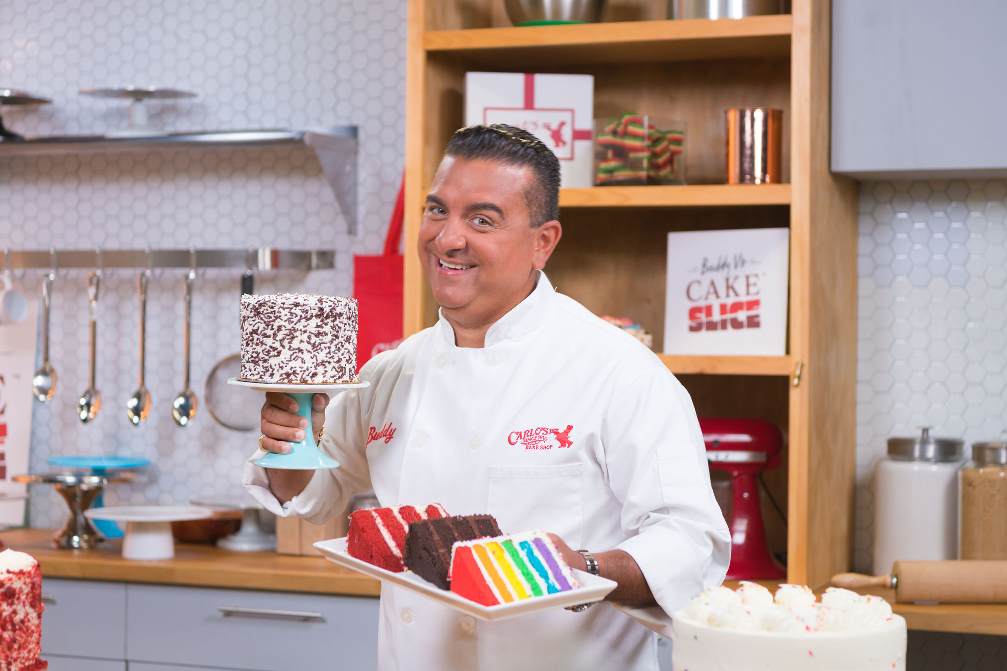 A man in a white chef's coat holds slices of red velvet, chocolate, and rainbow cake.