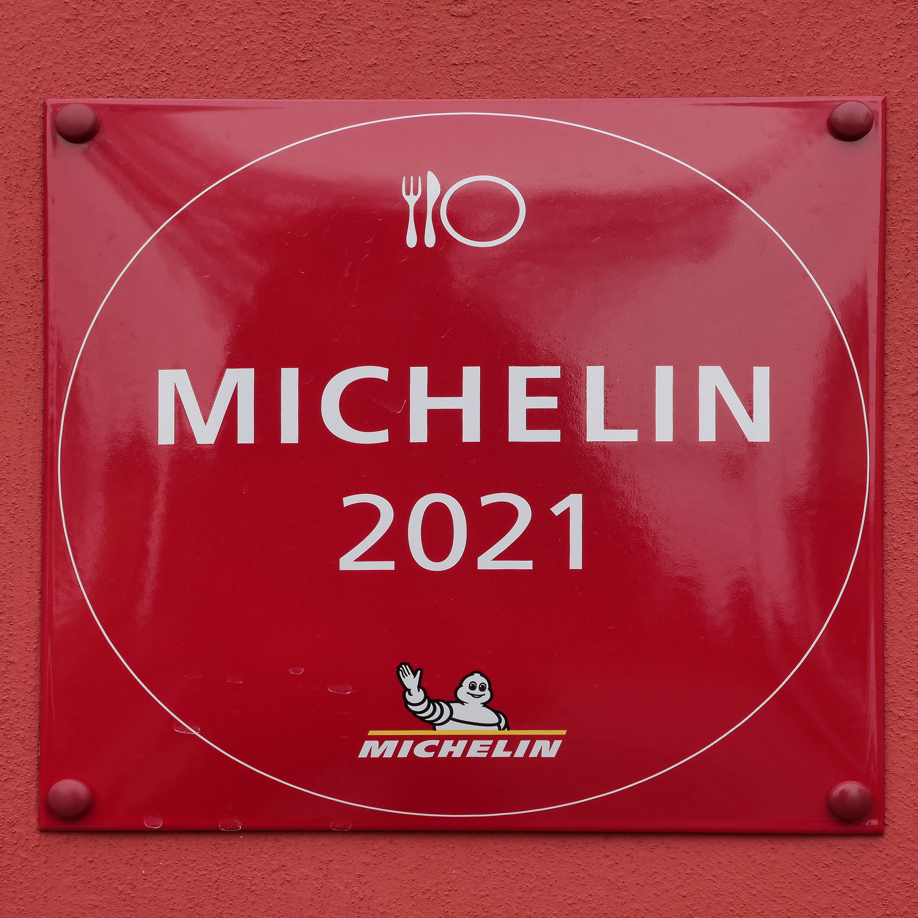 Sign for Michelin Guide 2021 on a red wall.