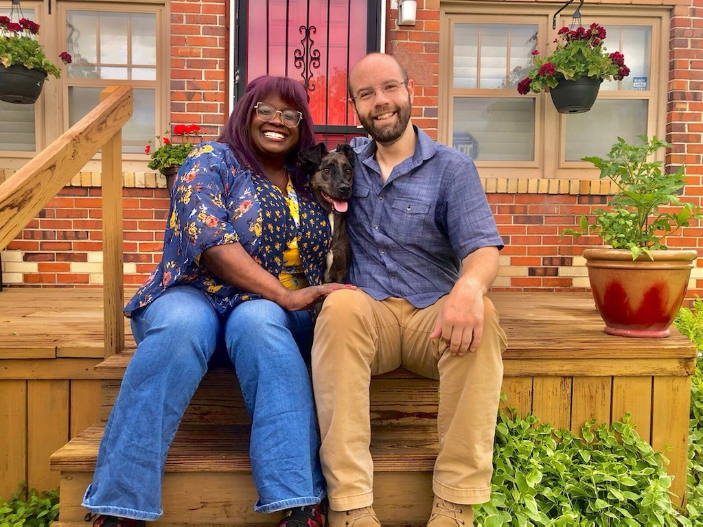 A man and a woman sit on a wooden porch. They are smiling at the camera. There is a dog between them with its tongue out.