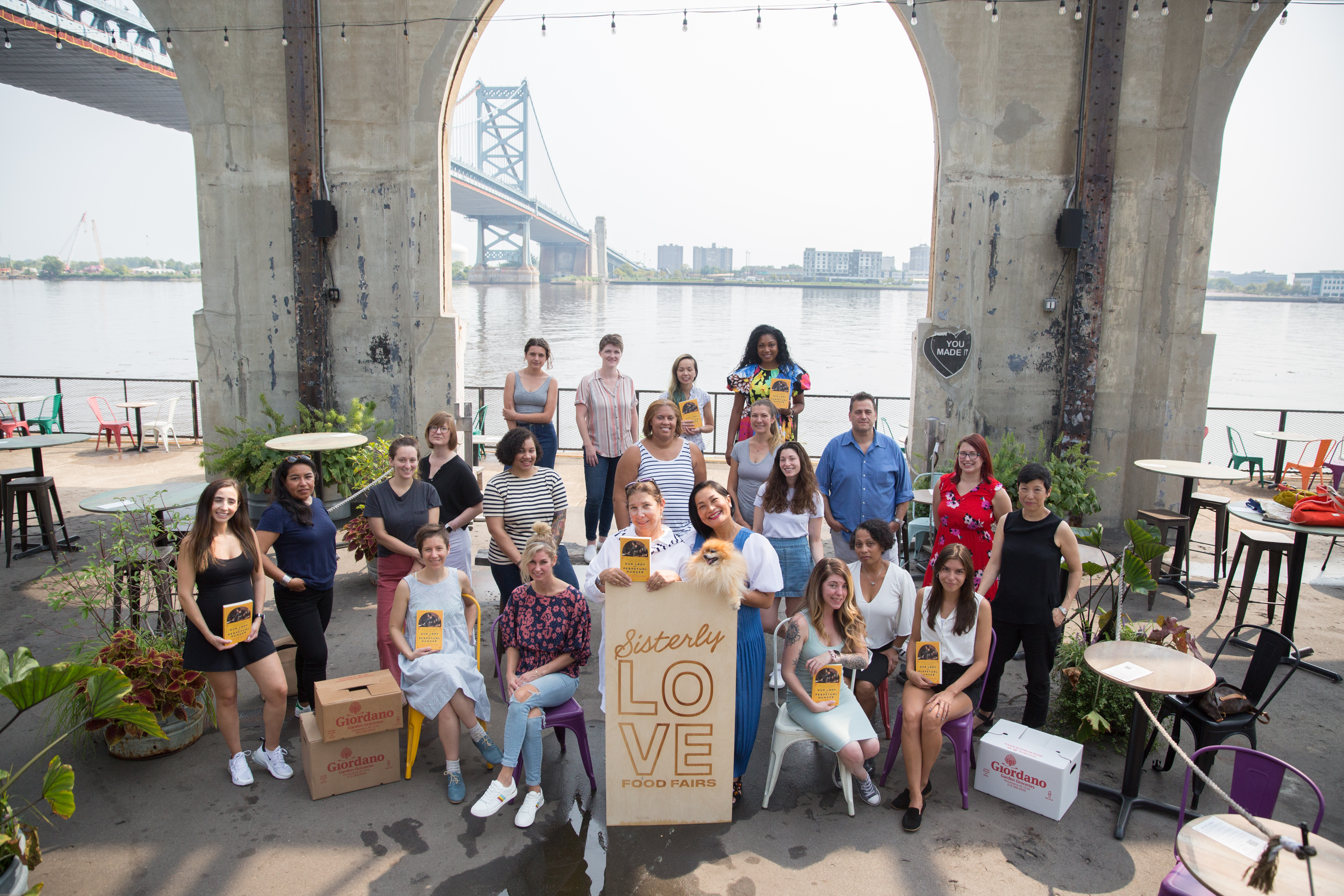 a group of women gather on a pier in front of a sign for Sisterly Love Food Fair