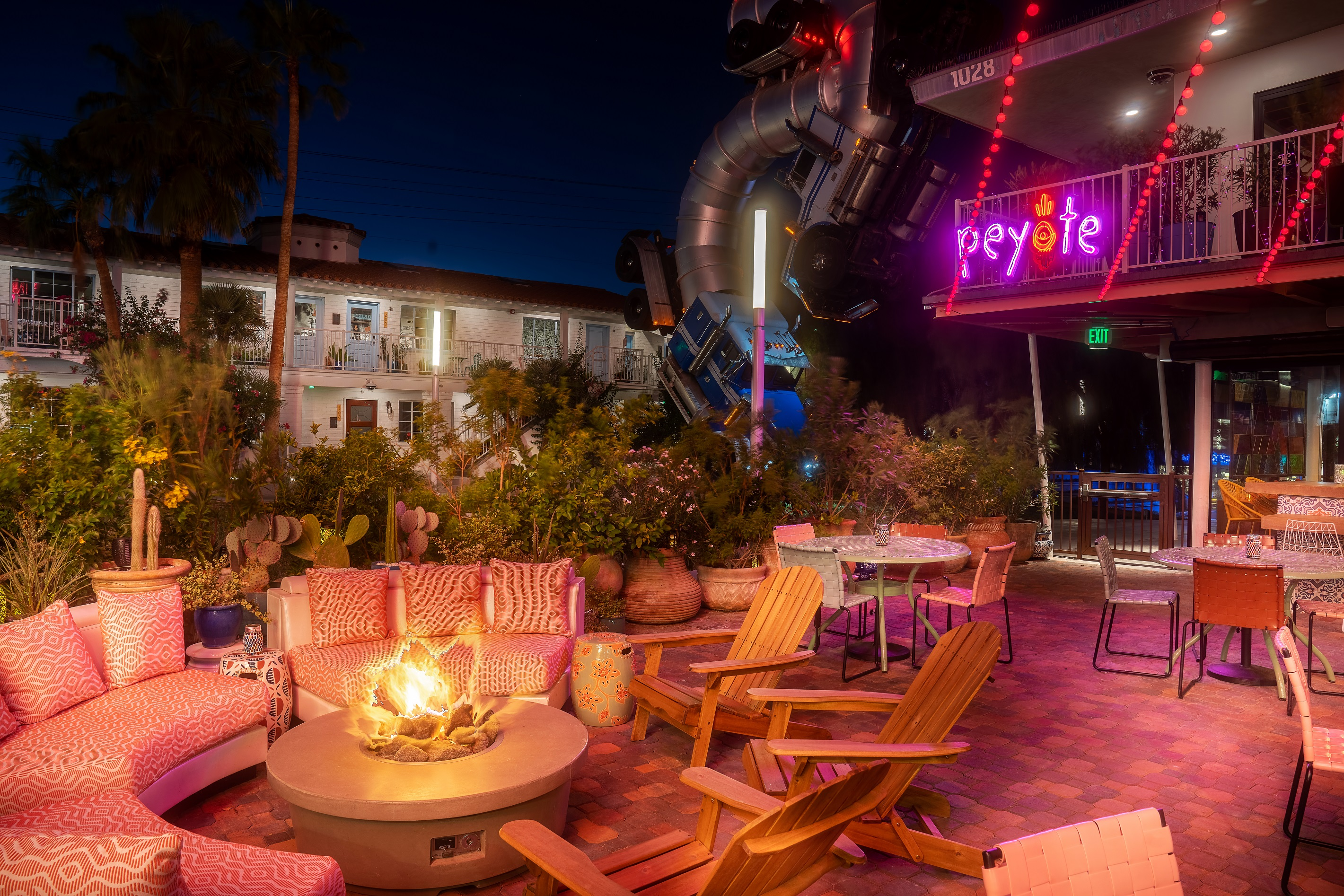 A patio with chairs and tables and a neon sign at night.