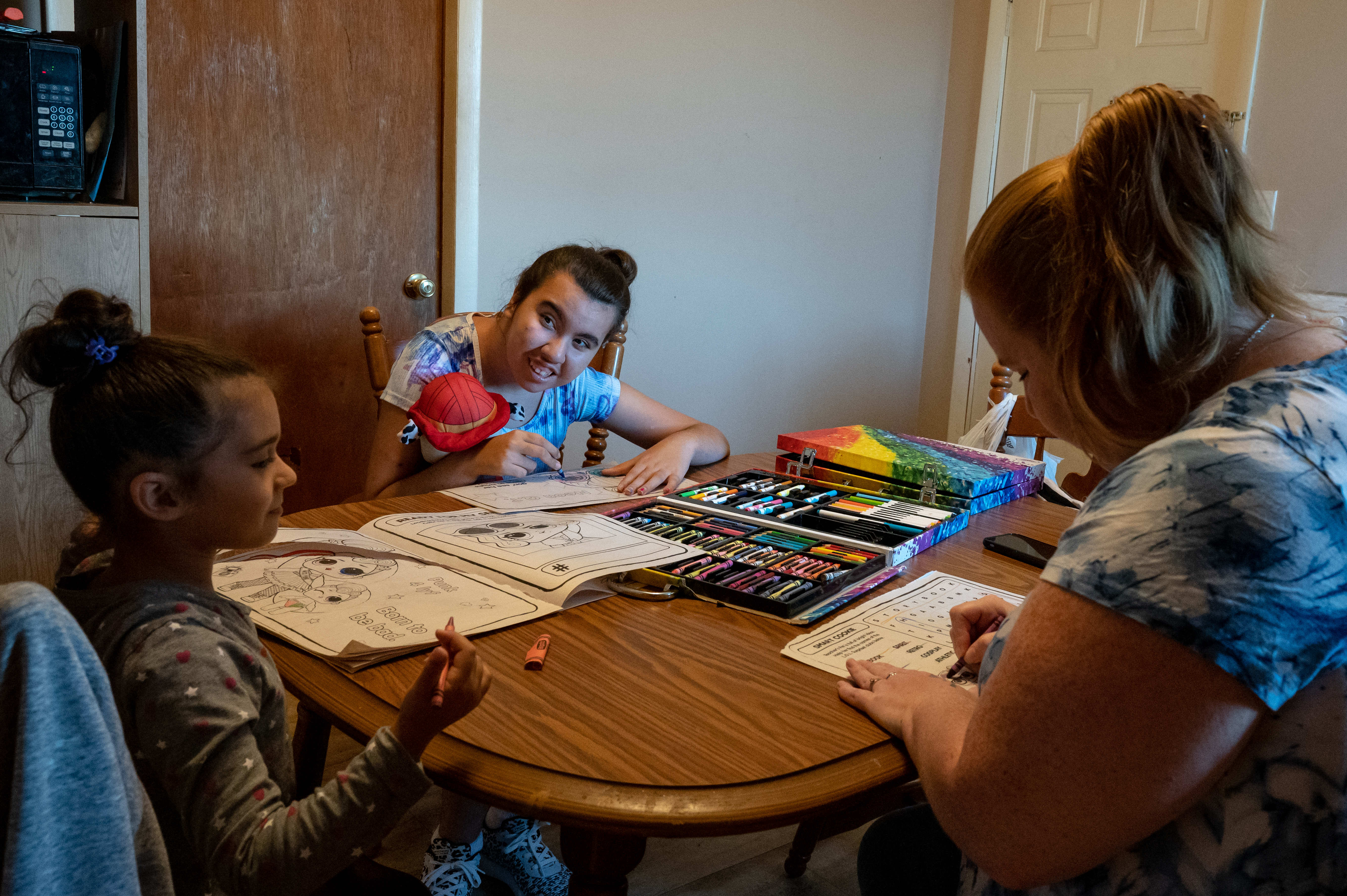 Two girls and a woman color in coloring books together at a dining room table.