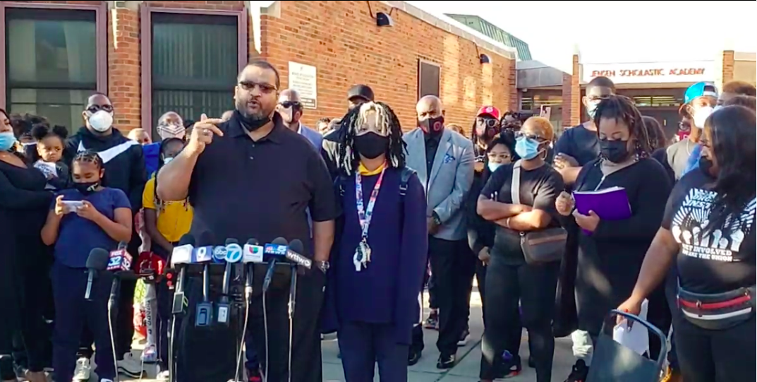 Shauntee Colston, a parent at Jensen Elementary on Chicago's West Side, stands behind a stand of microphones, outside the school building with his daughter, who is wearing a face mask, and other parents.