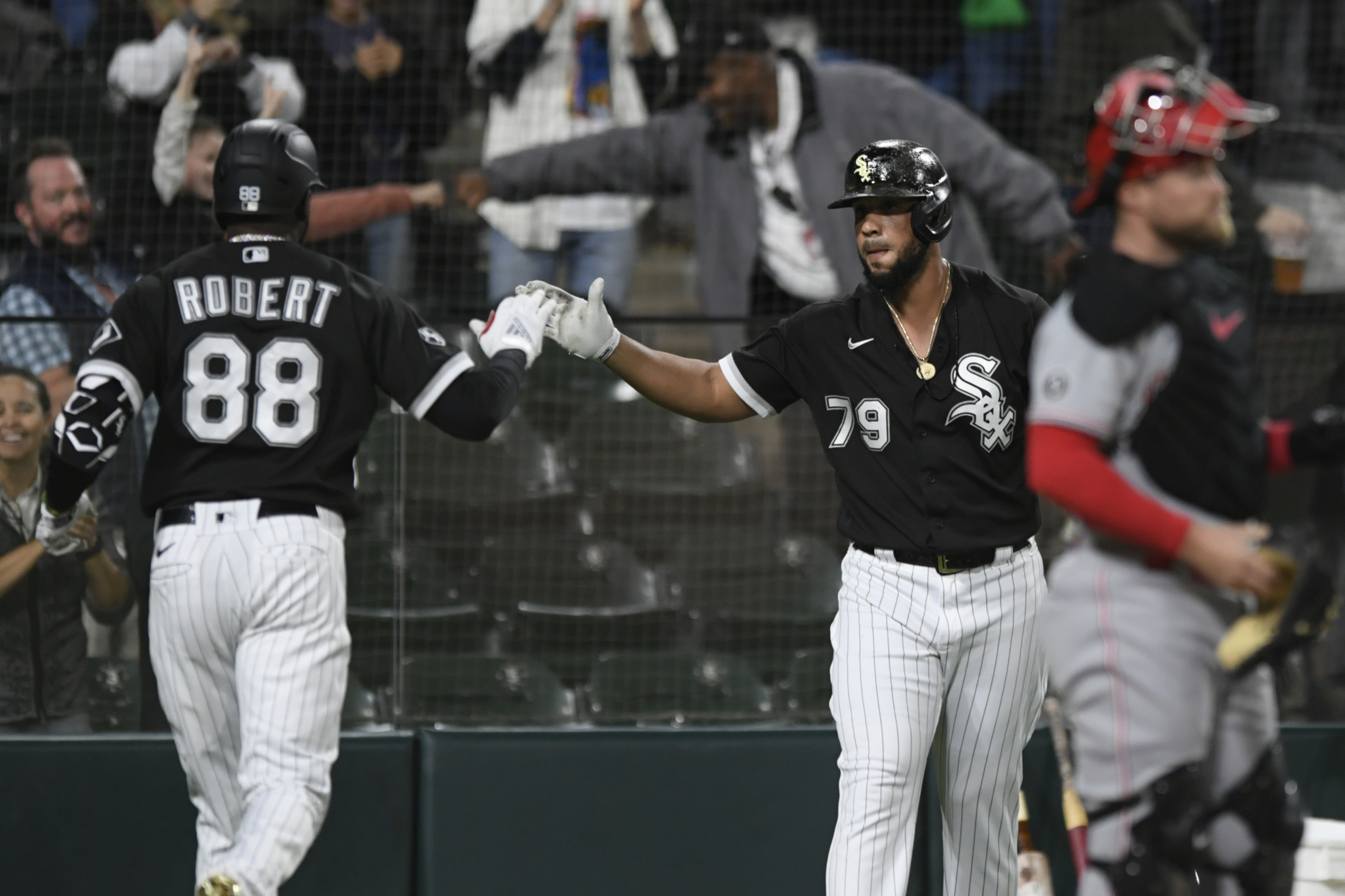 White Sox center fielder Luis Robert (88) celebrates with teammate Jose Abreu after hitting the first of two home runs against the Cincinnati Reds on Tuesday.