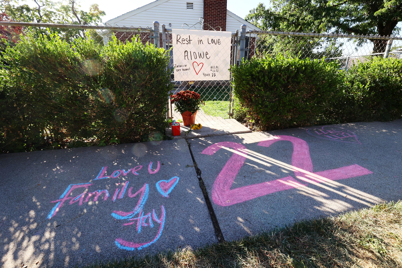 "A memorial for University of Utah sophomore defensive back Aaron Lowe, with ""22"" written on the sidewalk in chalk"