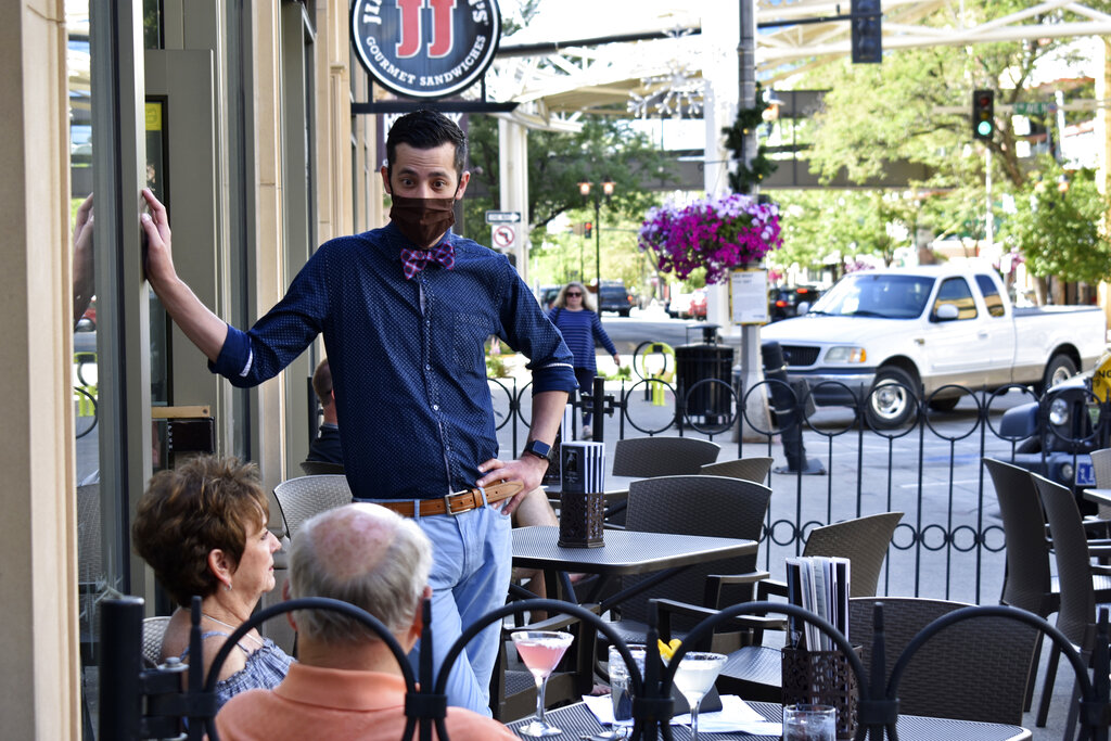 An employee of Doc Harper's Tavern talks with customers while wearing a face mask in Billings, Mont.